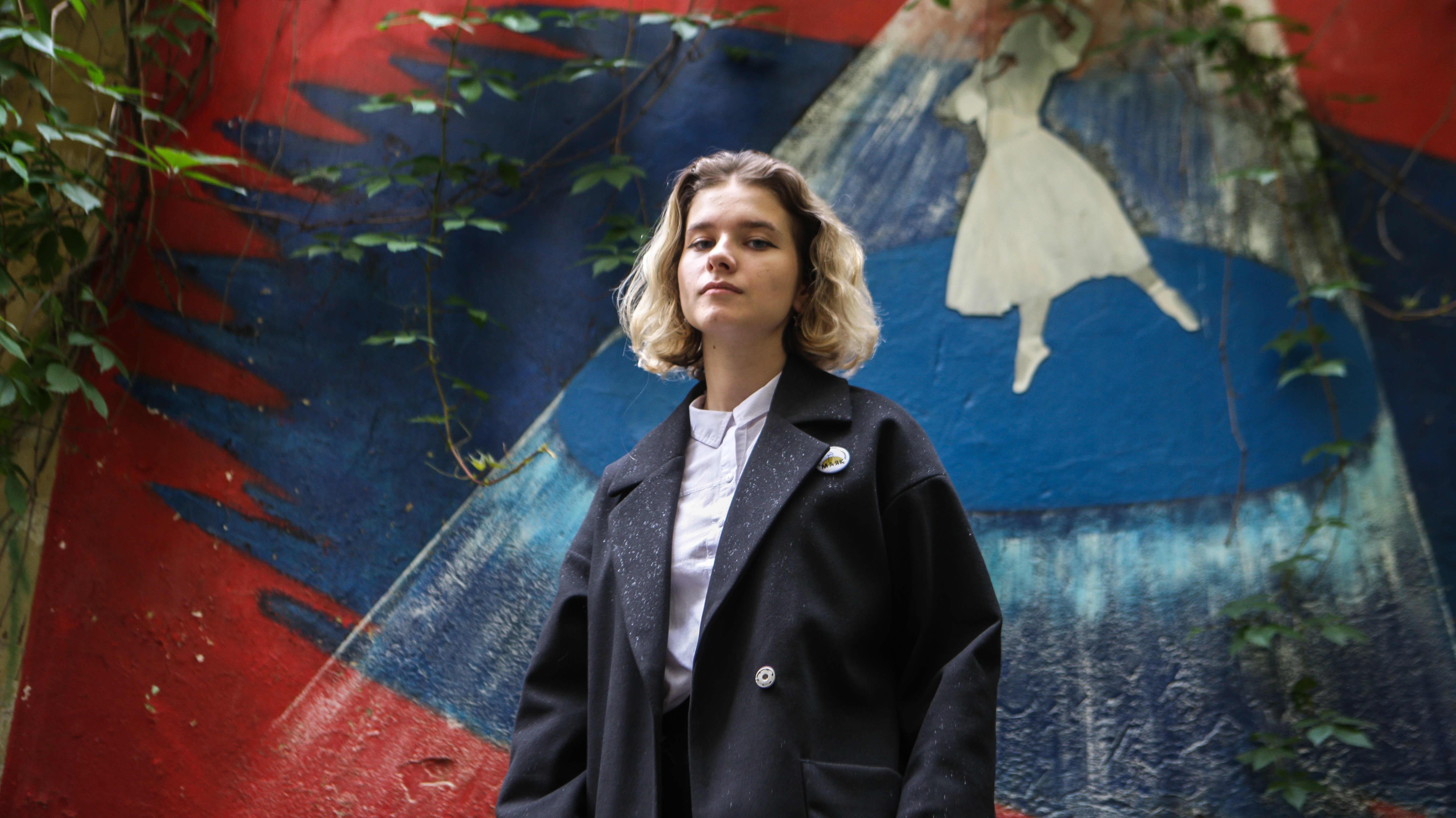 Darja Heikinen katsoo kameraan, taustalla puna-sini-valkoinen muraali, jossa balleriina