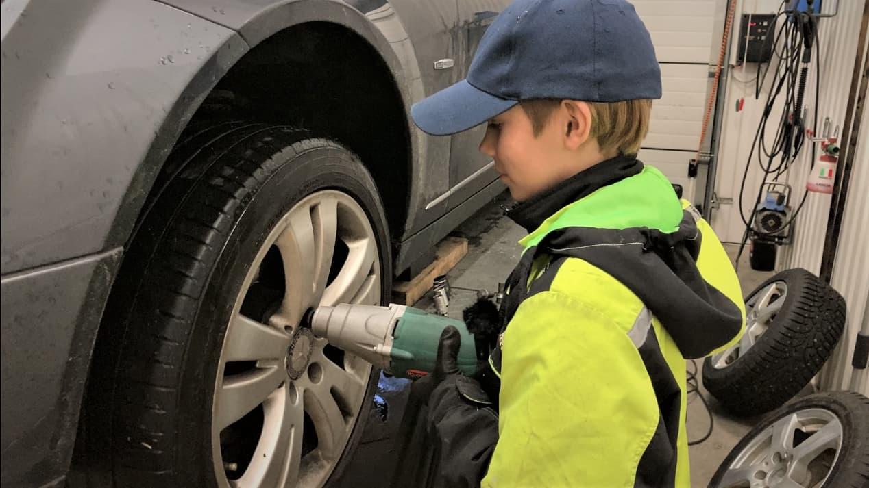 13-vuotias Aati Junttila vaihtaa autoon talvirenkaita Seinäjoella tallissa.