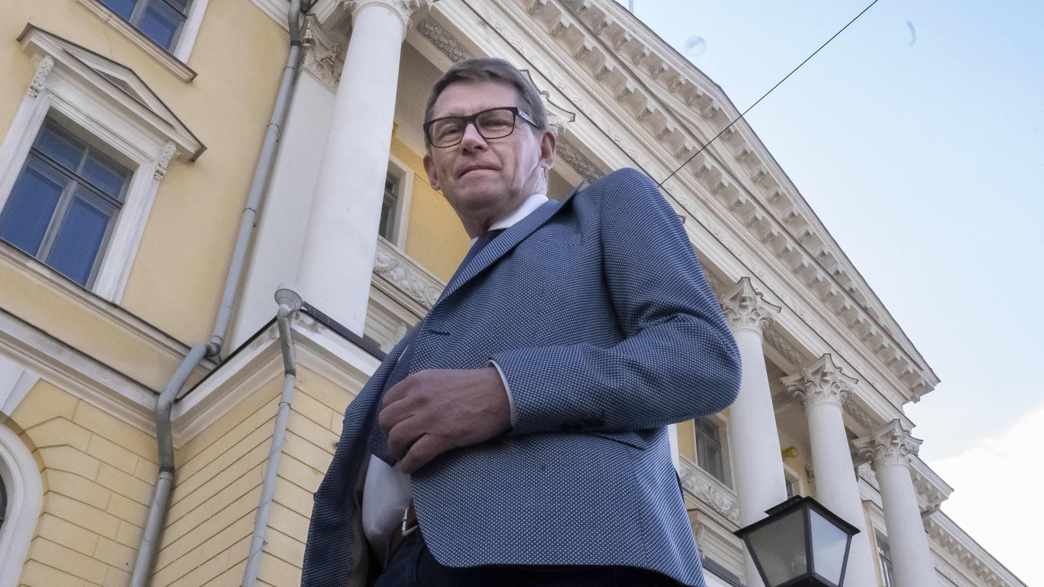 Ministeri Vanhanen poseeraa Valtionneuvoston linnan edessä.