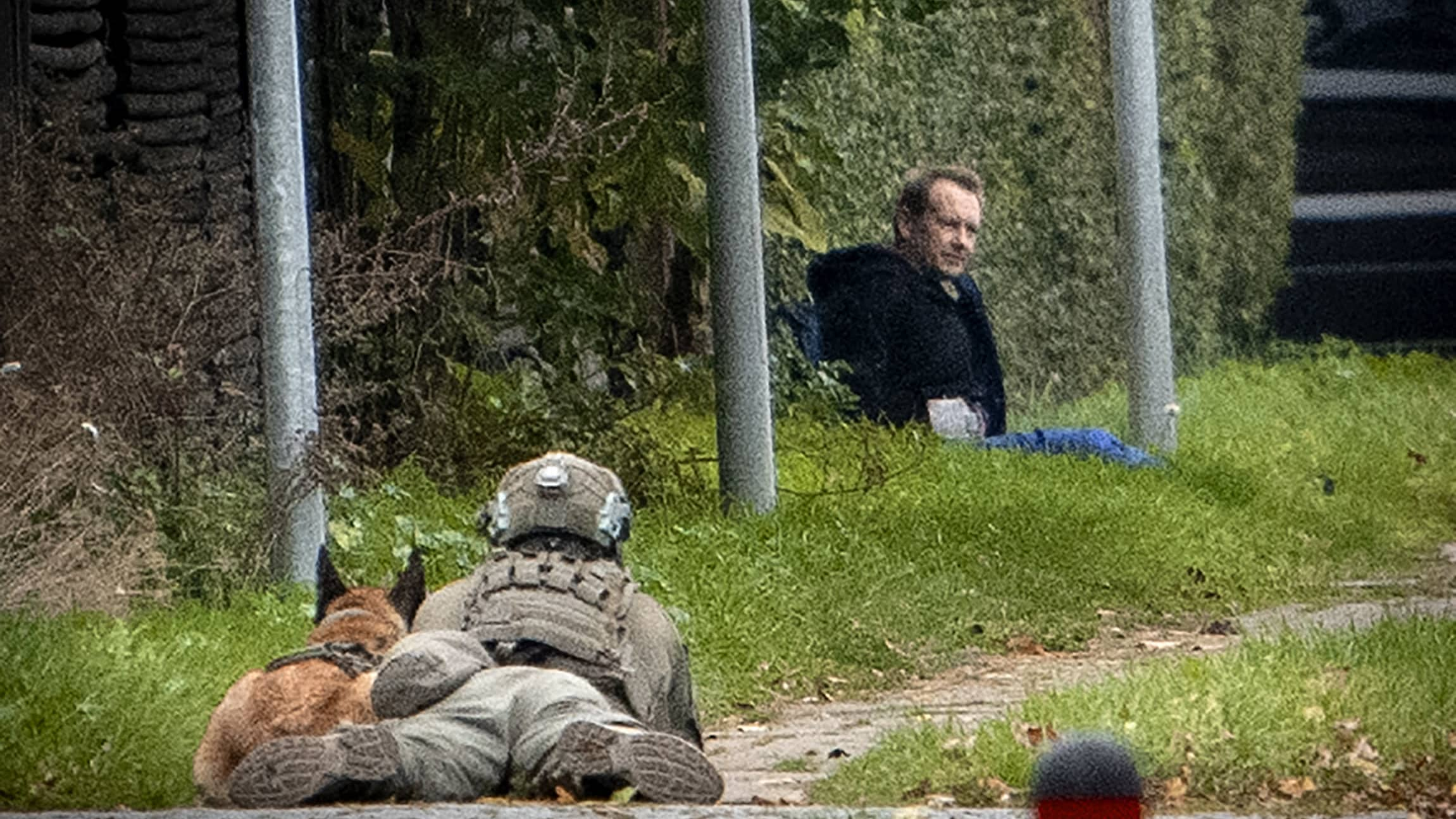 Mies koira koira vieressään vahtii maassa istuvaa Peter Madsenia.