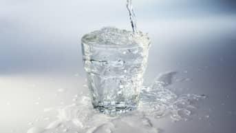 Vettä kaadetaan juomalasiin
