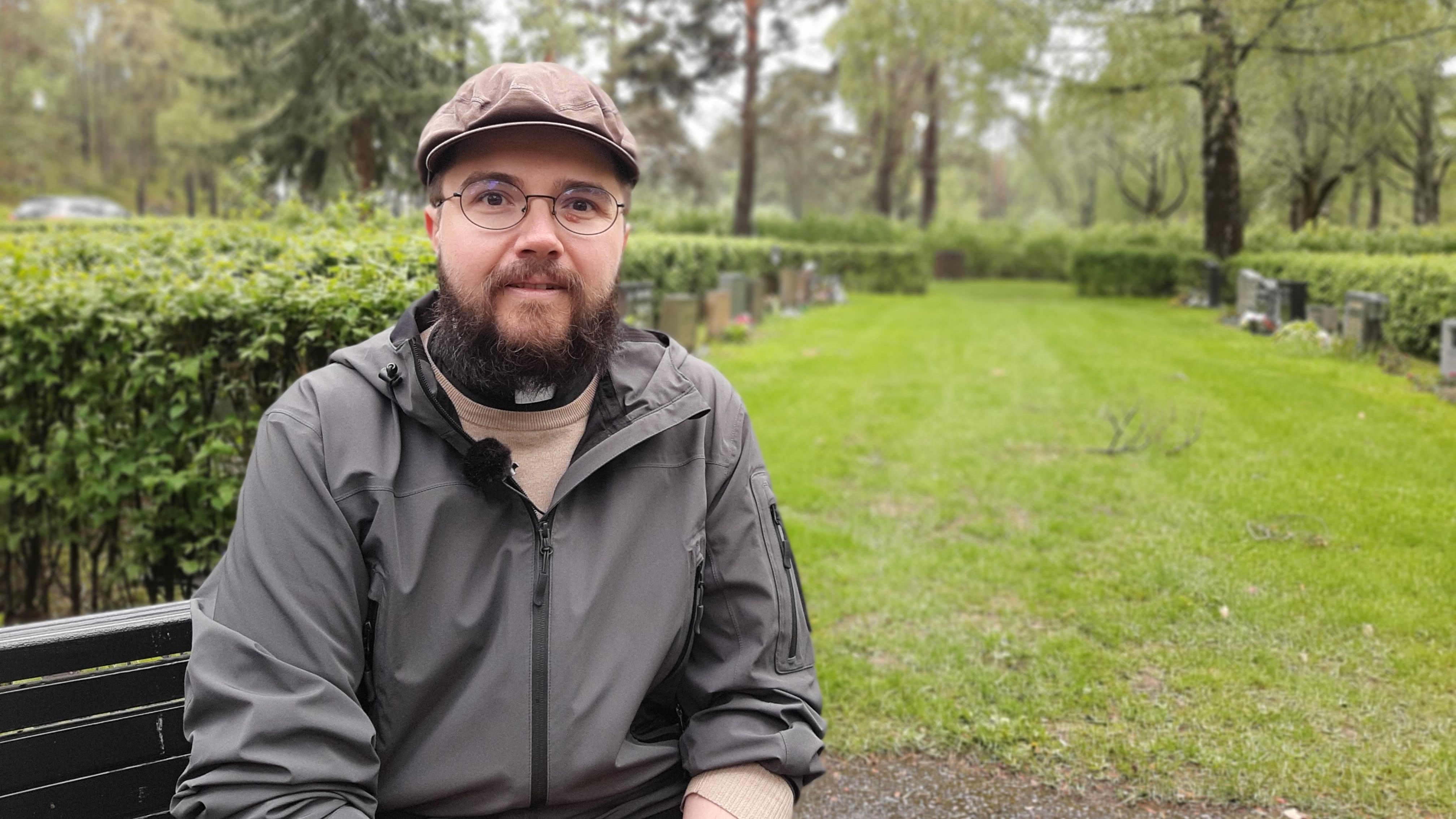 Begravningsplatsprästen Peter Eriksson, en man med skärmmössa, skägg och vit prästkrage, sitter på en bänk bland gravar.