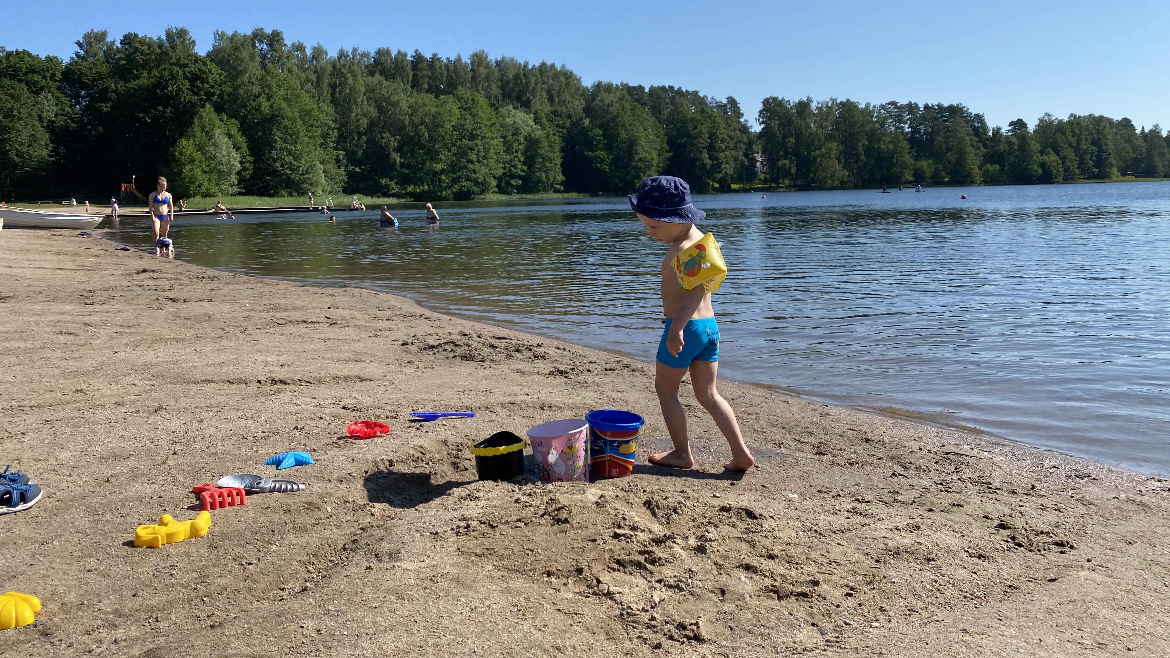 Lapsi leikkii hiekkarannalla