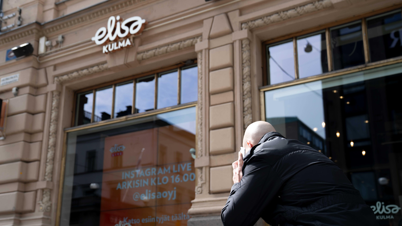 Mies puhuu puhelimeen Elisa-kaupan edessä.