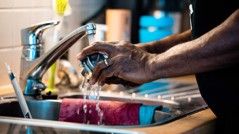 Henkilö pesee astioita.