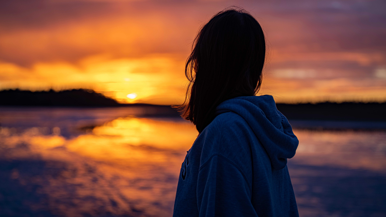Nuori henkilö katsoo auringonlaskua.