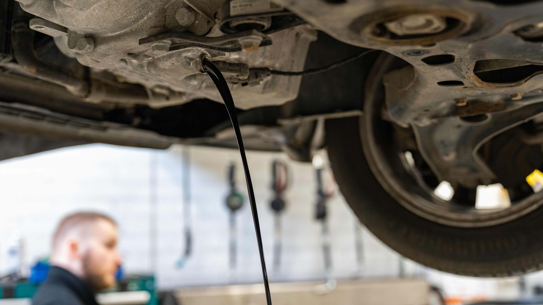 yleiskuva - käytetty, musta öljy valuu auton moottorin öljysäiliön pohjassa olevasta poistoreiästä