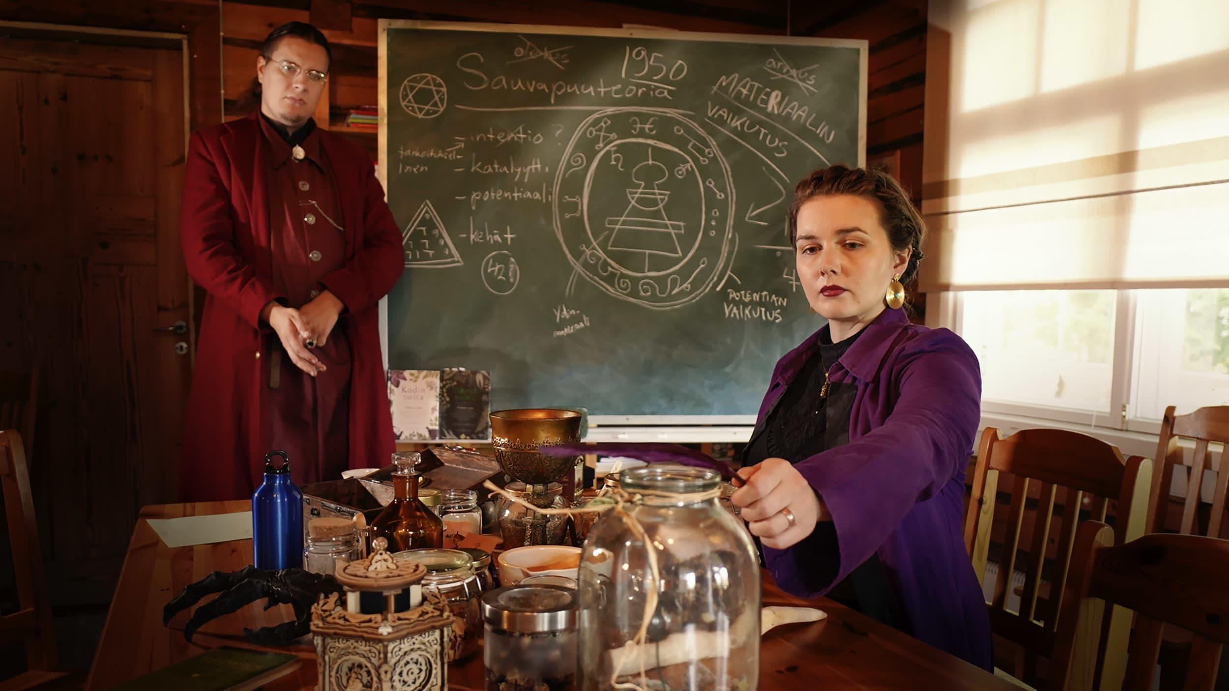 Janina Kahela istuu pöydän ääressä, joka on täynnä taikakoulularin rekvisiitta. Ville Miettinen seisoo taustalla liitutaulun vieressä. He ovat pukeutuneet rooliasuihinsa.