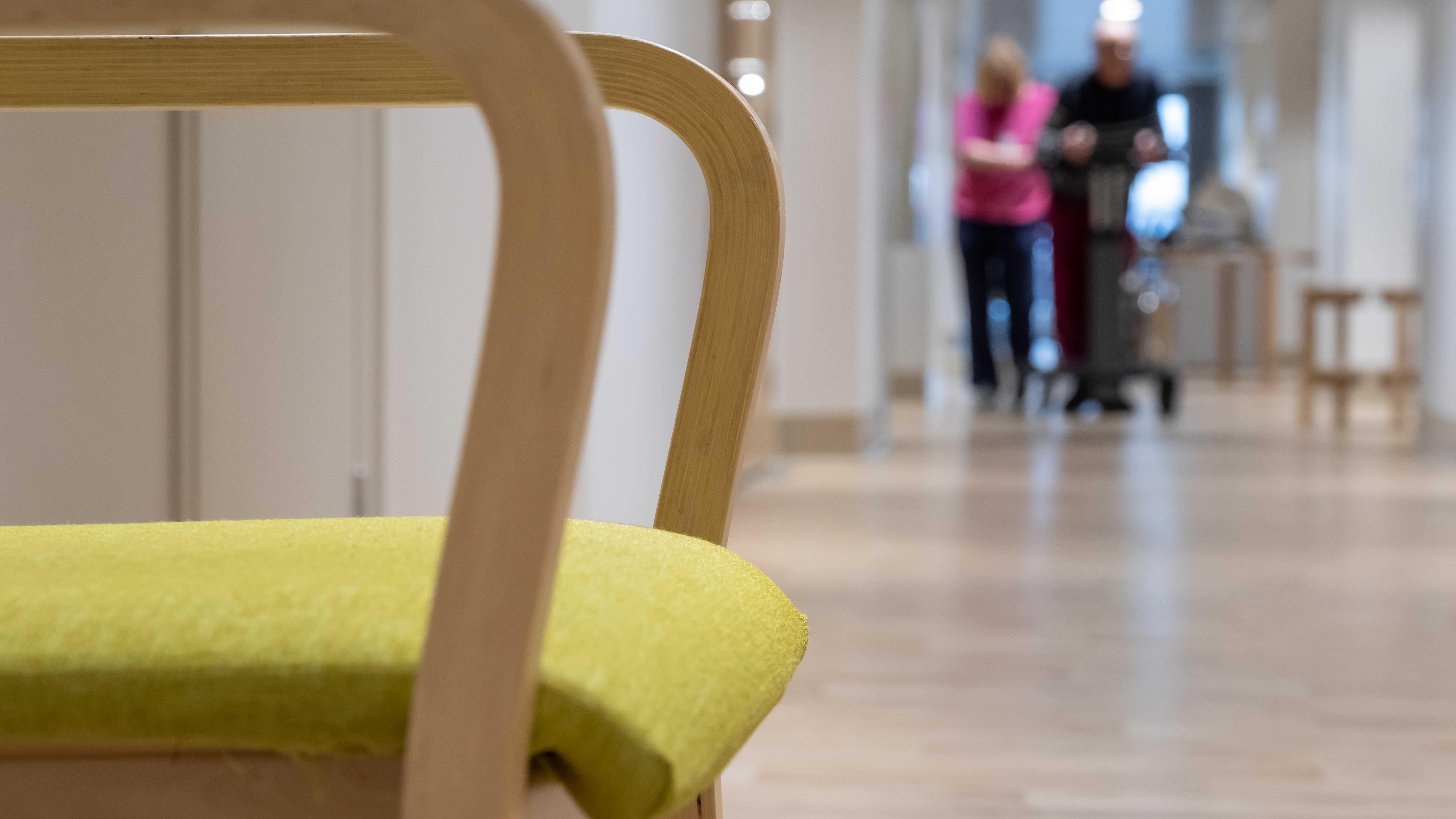 Fysioterapeutti avustaa vanhusta kävelyharjoituksessa Myyrmäen vanhustenkeskuksessa. Etualalla kuvassa tuoli.