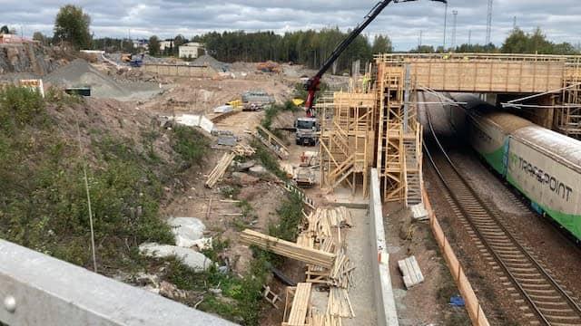 Hyväntuulentie katkaistuna. Rakennustyömaa, puisia rakennustelineitä ja junaraide.