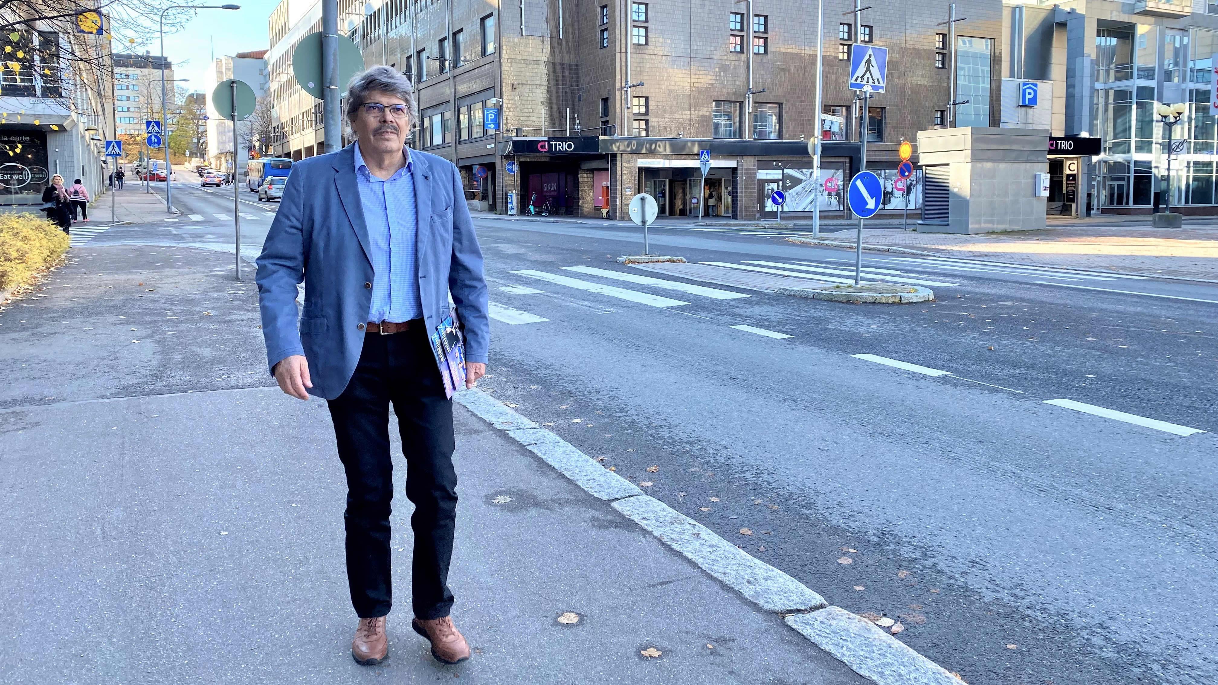 Kirjailija Timo Sandberg kävelee kadulla, taustalla kaupunkinäkymä ja kauppakeskus Trio Lahdessa.