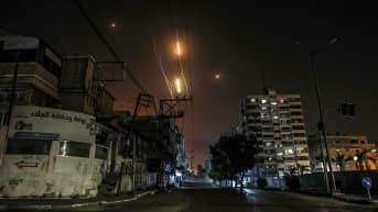 Kaksi rakettia näkyy valojuovina taivaalla asuintalojen yllä.