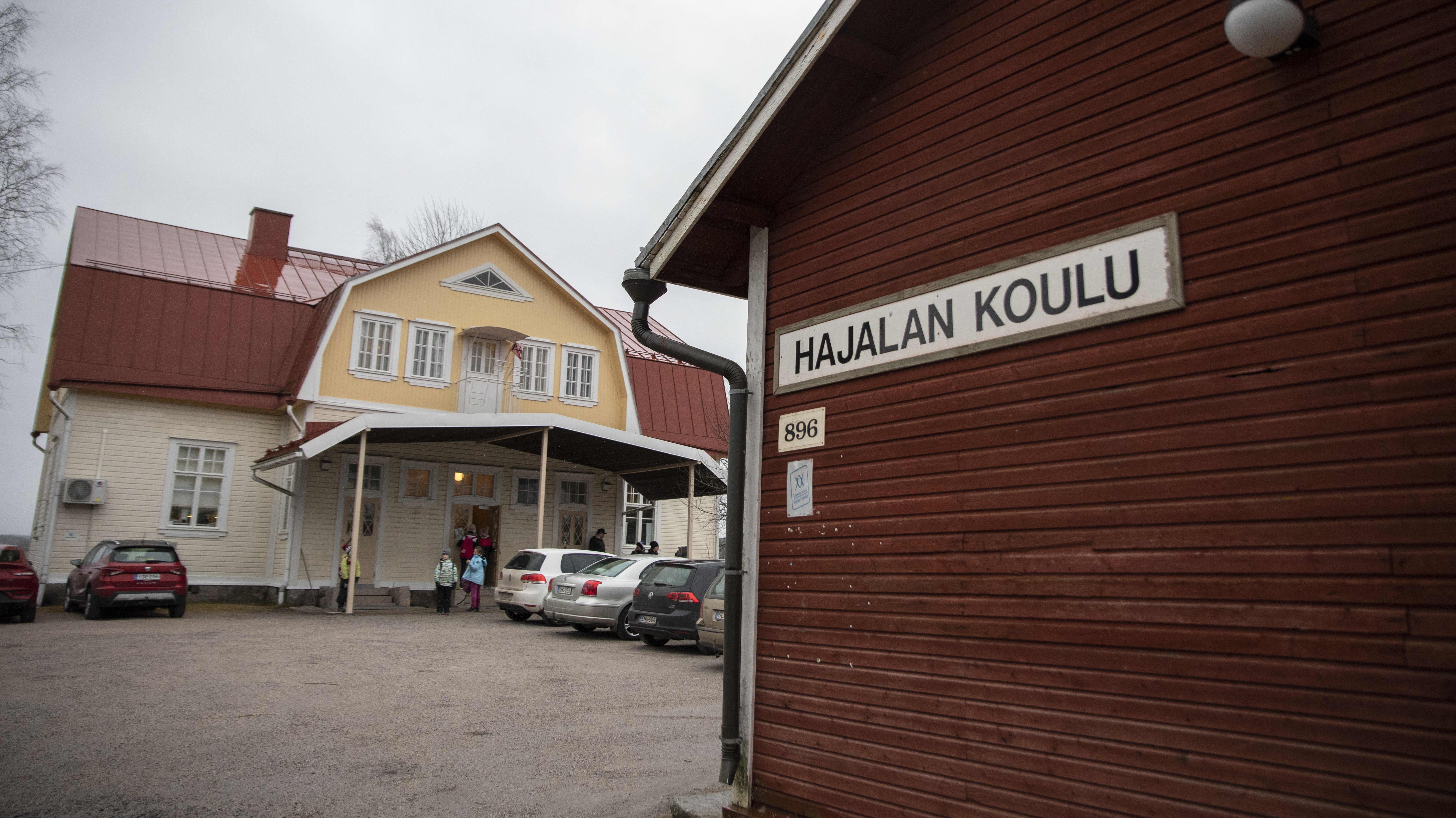 Ulkokuva Hajalan koulusta ja koulun kyltistä.