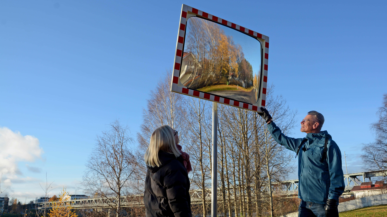 Aku Raappana ja Jenni Lintula laittavat suoraan peiliä vaarallisessa mutkassa, jossa näkyvyys on huono pensasaidan ja tiukan kurvin vuoksi.