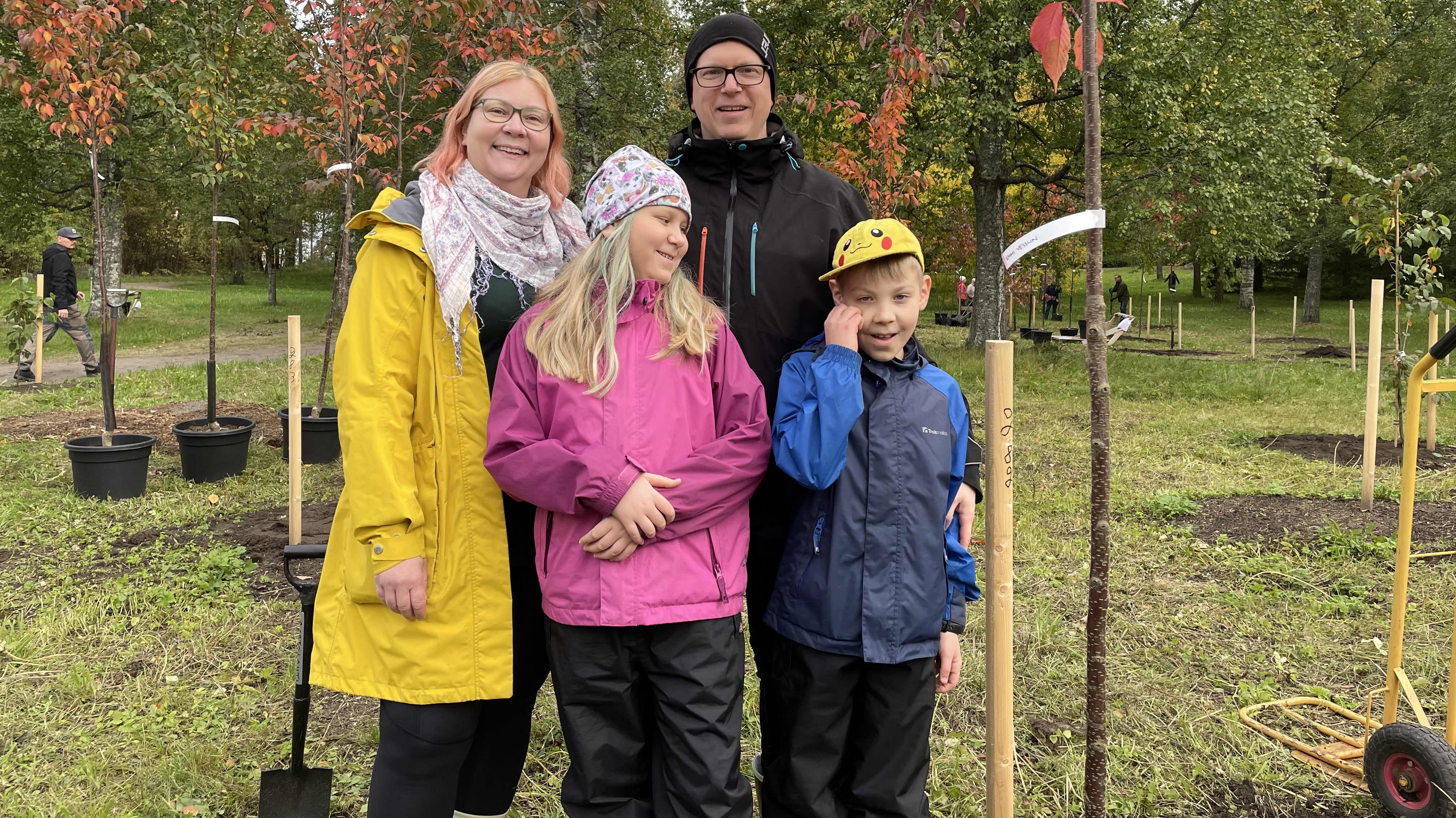 perhe vesslin kirsikkapuunsa vieressä