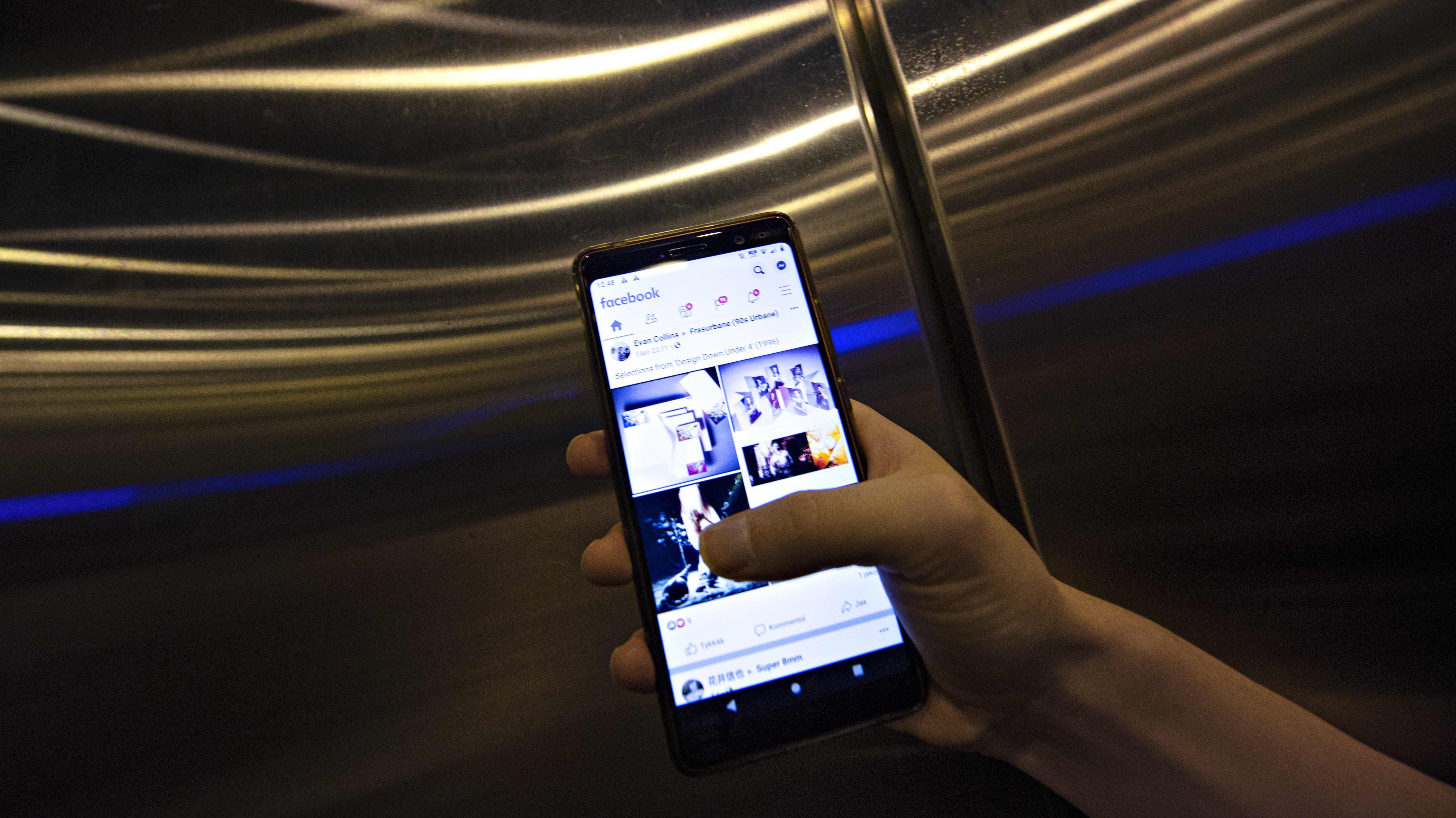Mies käyttää Facebook-sovellusta älykännykällä.
