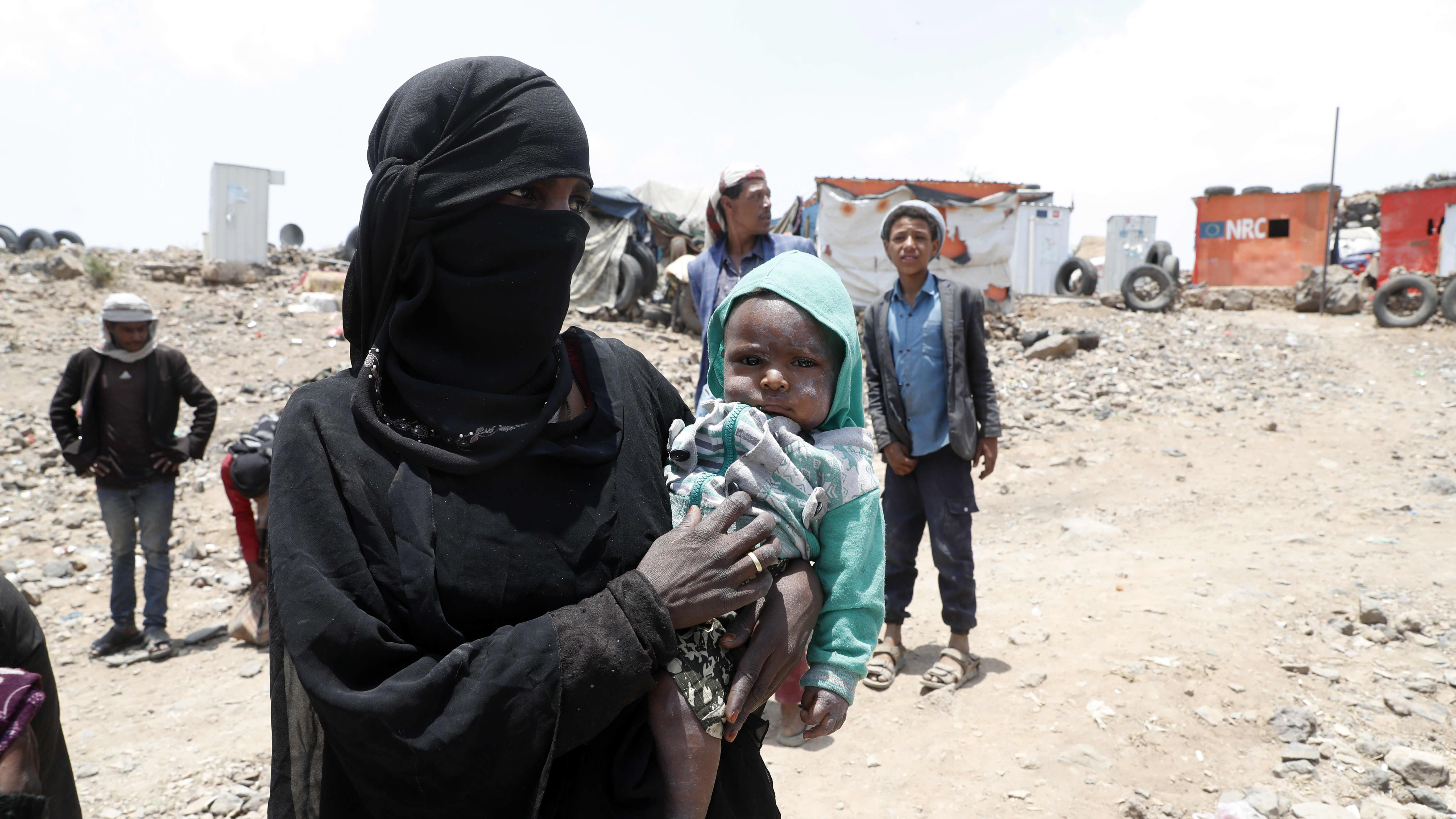 Jemeniläinen äiti pitää sylissään lastaan pakolaisleirillä Sanaan kaupungin ulkopuolella.