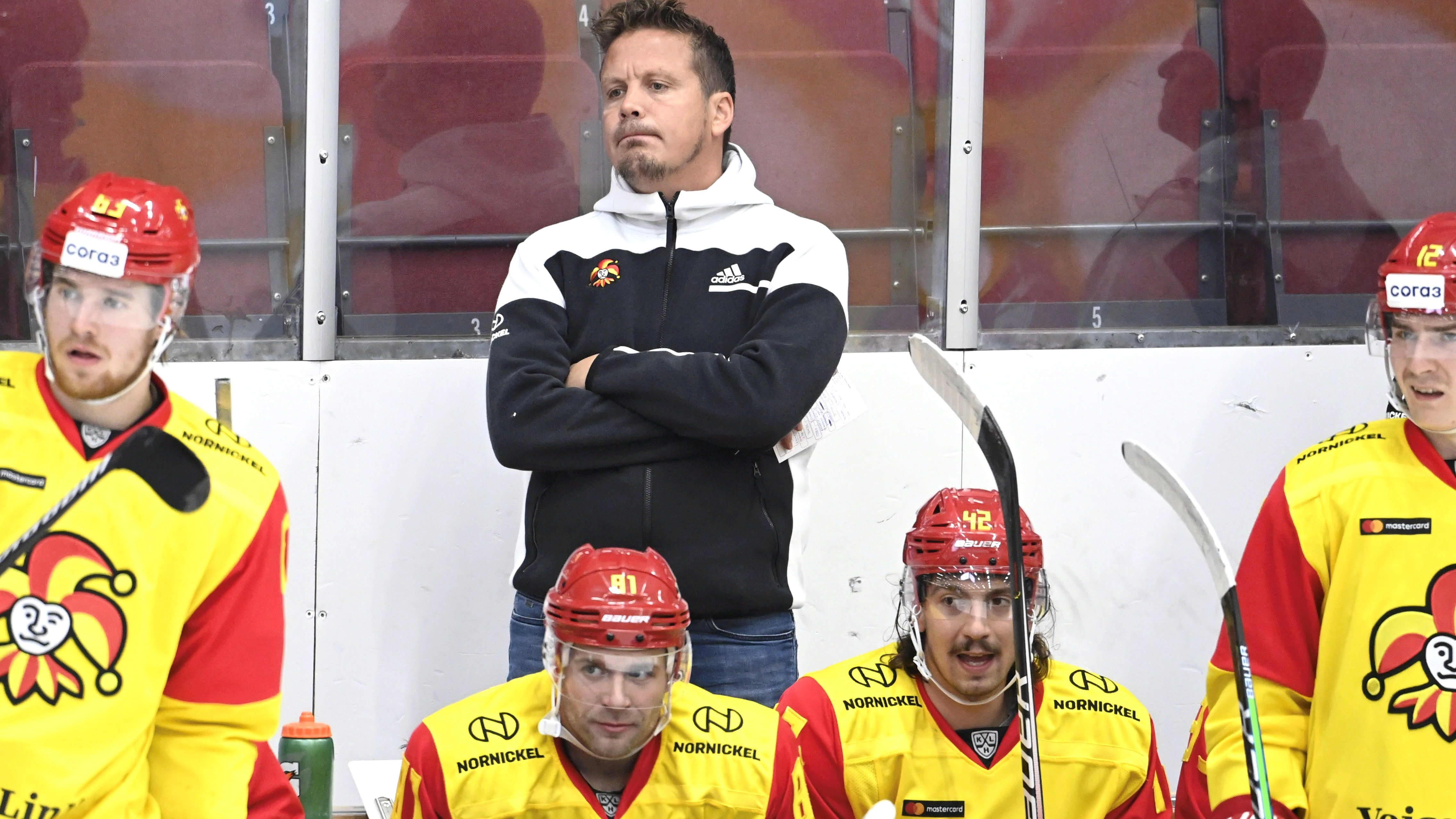 Jokerien vaihtopenkkiä, jonka takana päävalmentaja Lauri Marjamäki mietteliäänä.