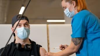 Sakari Siika-aho (vas) saa ensimmäisen koronarokotteen terveydenhoitaja Maija Tilliltä, Jätkäsaaren rokotuspiste, Helsinki, 19.6.2021.