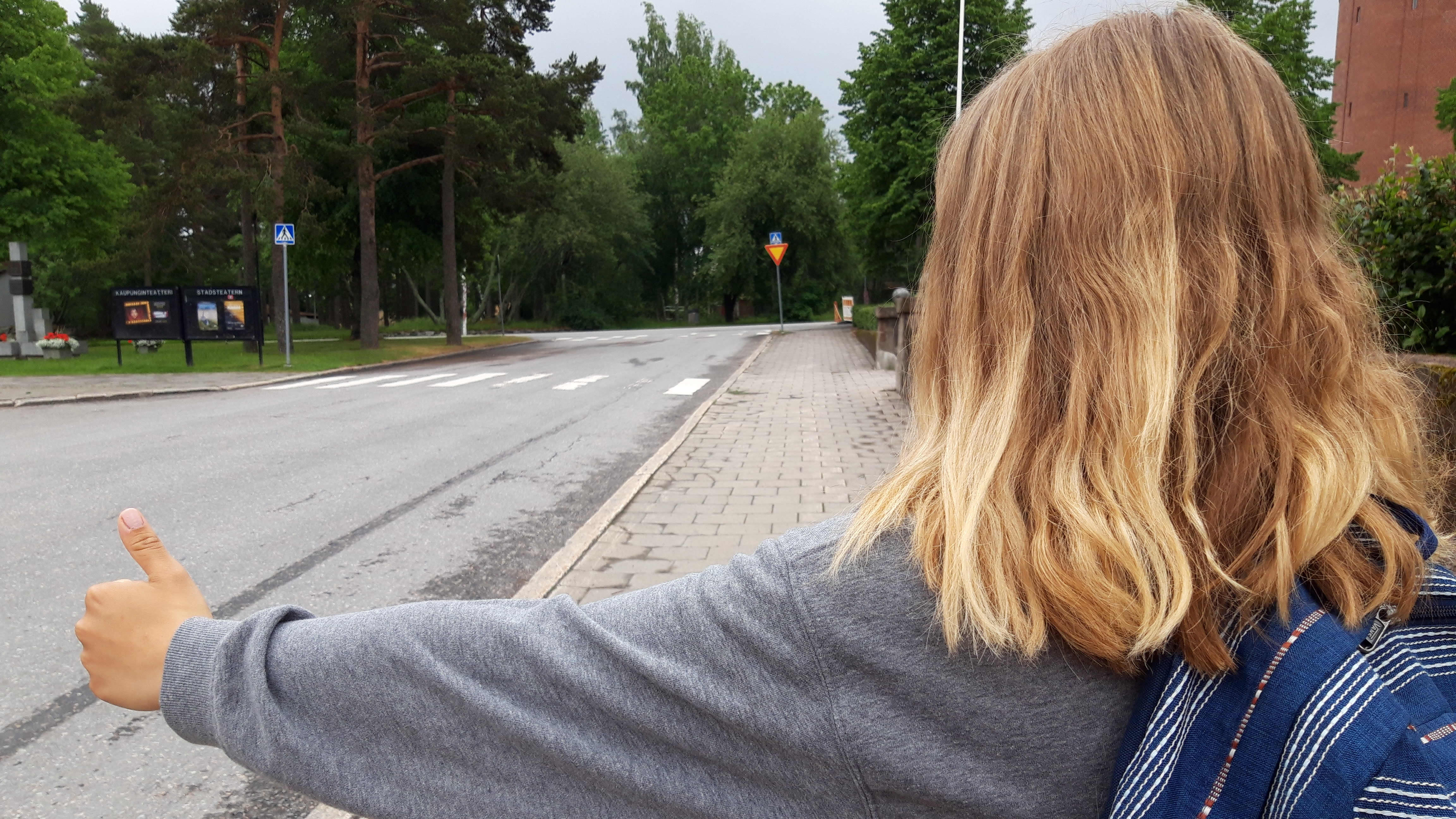 Selin oleva tyttö liftaa kadun reunassa.
