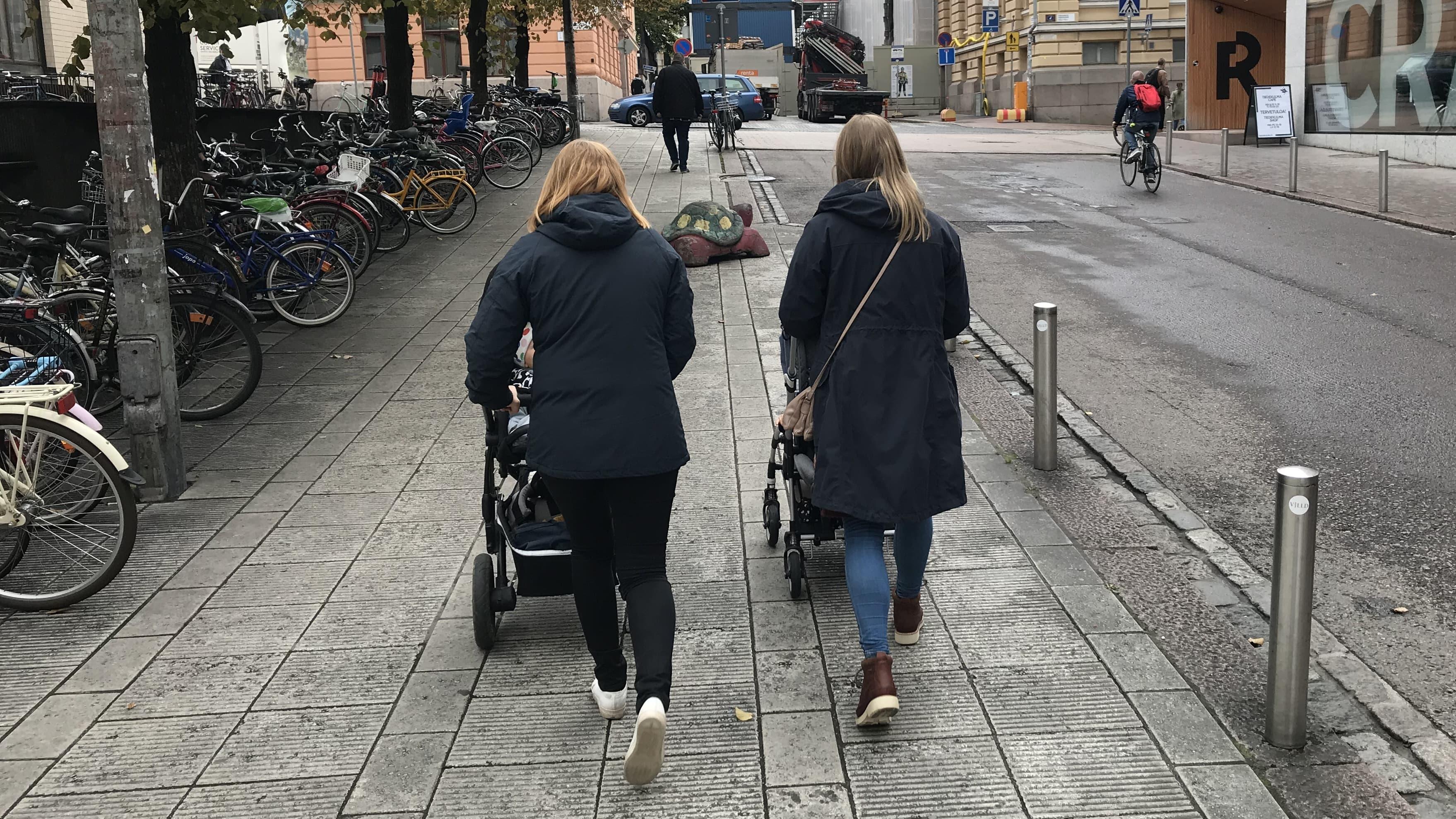 Kaksi äitiä työntää lapsia rattaissa.