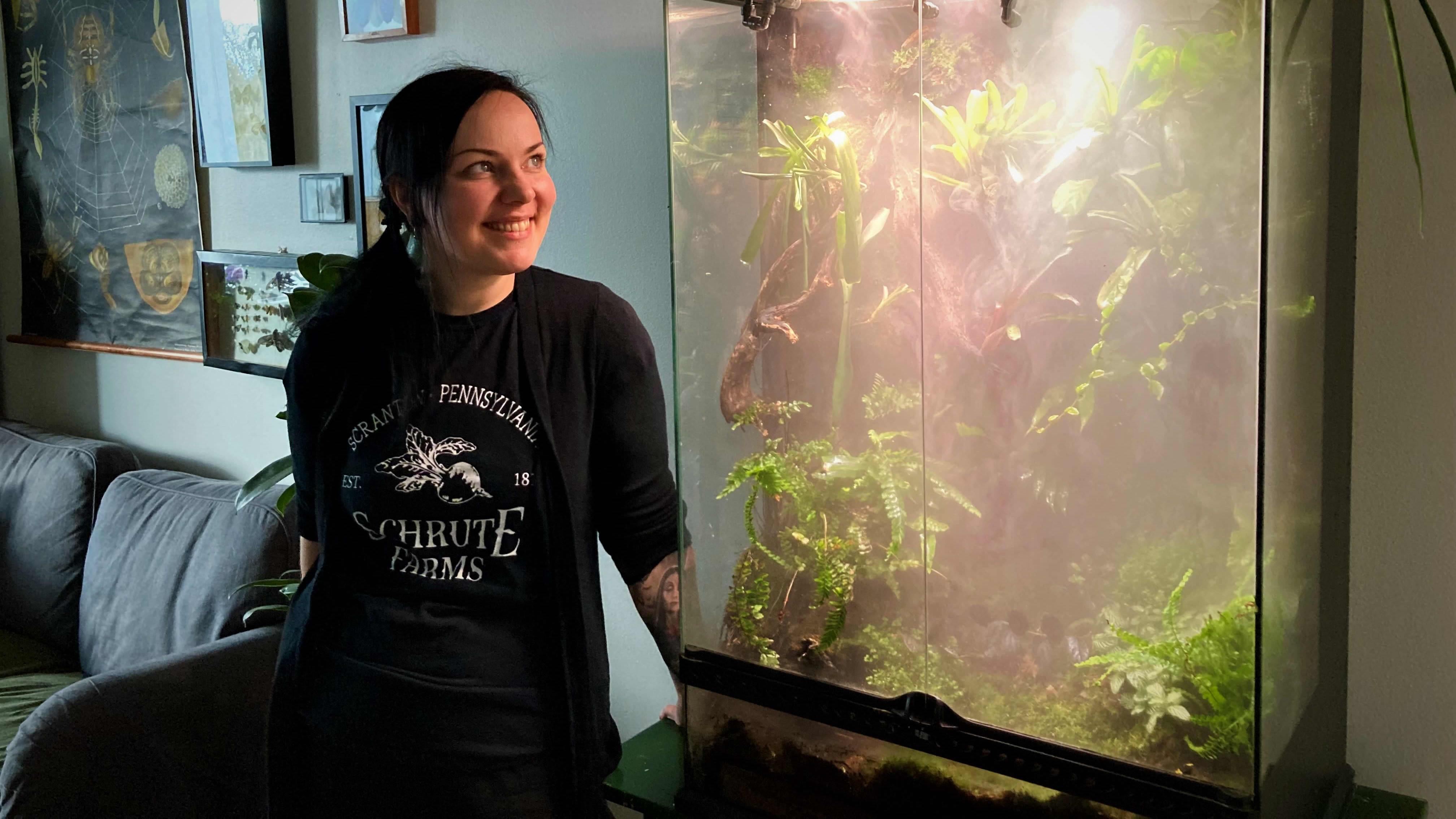 Laura Vuorenpää seisoo sumuisen terraarionsa vieressä