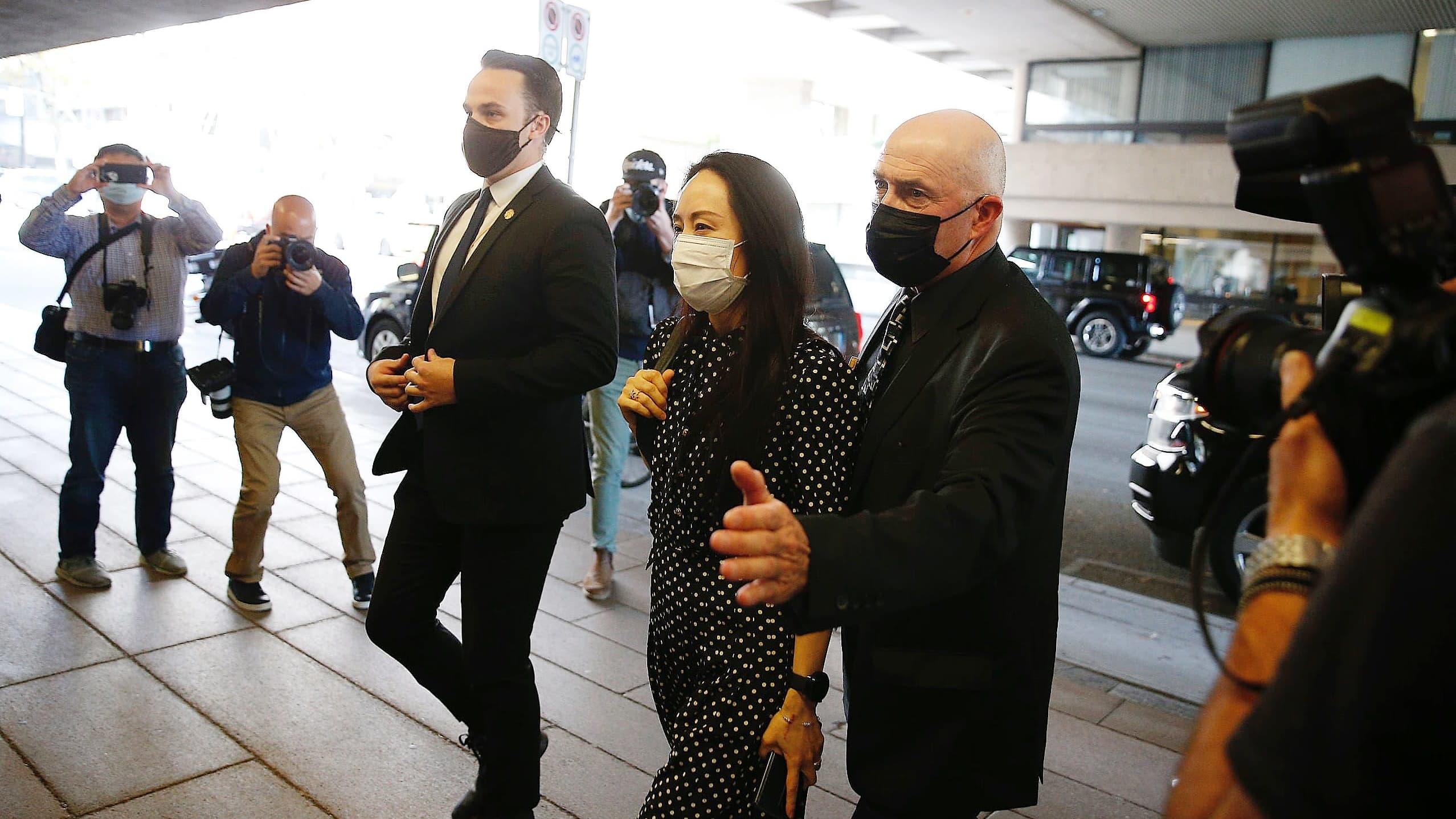 Kaksi tummapukuista miestä kulkee Meng Wanzhoun vierellä. Kaikilla on maskit kasvoillaan. Sivulla kuvaajat ottavat kuvia saapumisesta.