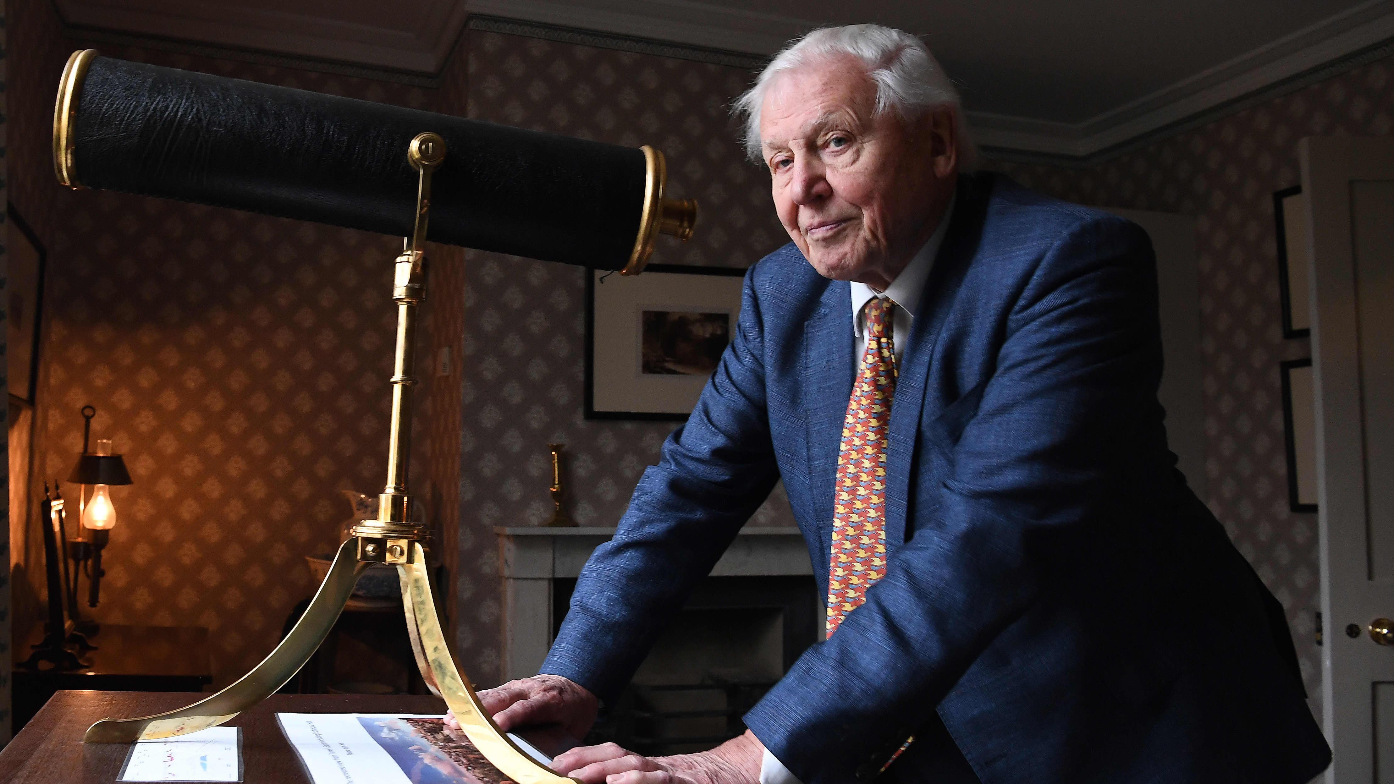 Sir David Attenborough poseeraa kaukoputken kanssa.