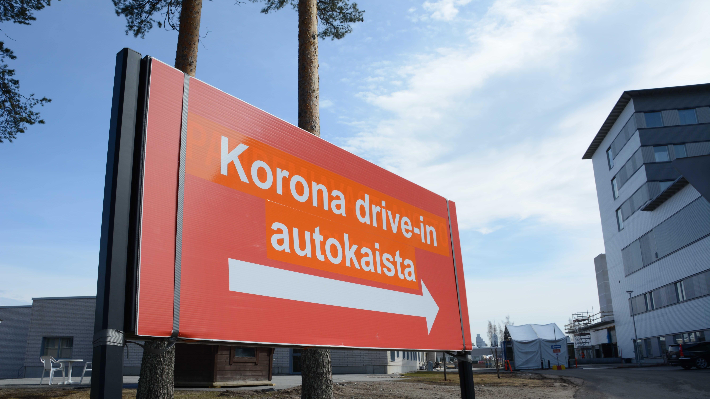 Iso oranssi kyltti Koronatestauksesta Kajaanin keskussairaalan pihassa. Taka-alalla näkyy teltta, jossa drive-in -testaukset suoritetaan.