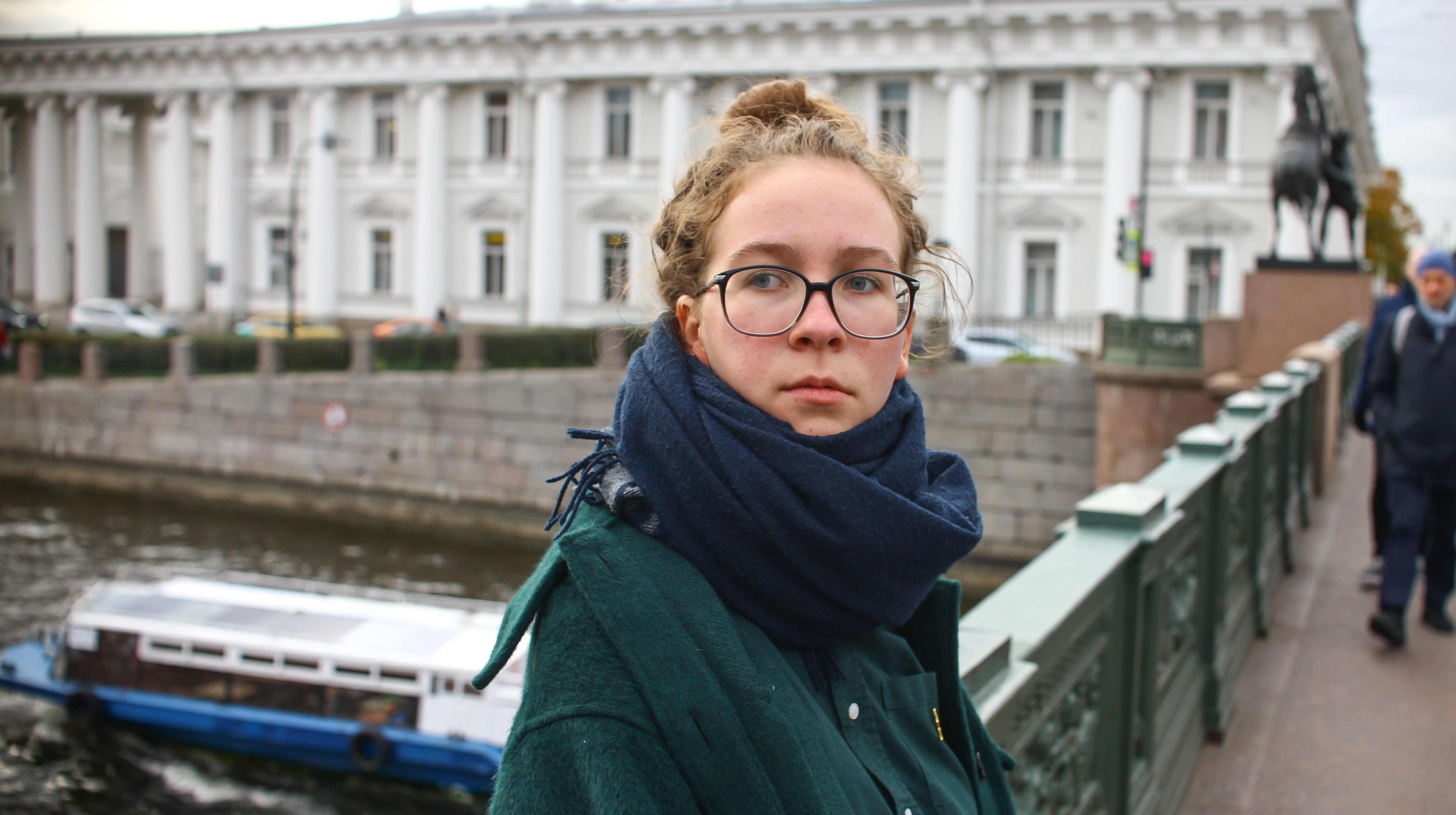 Tasja Kondratjeva nojaa sillankaiteeseen, taustalla turistivene palatsi pylväineen.