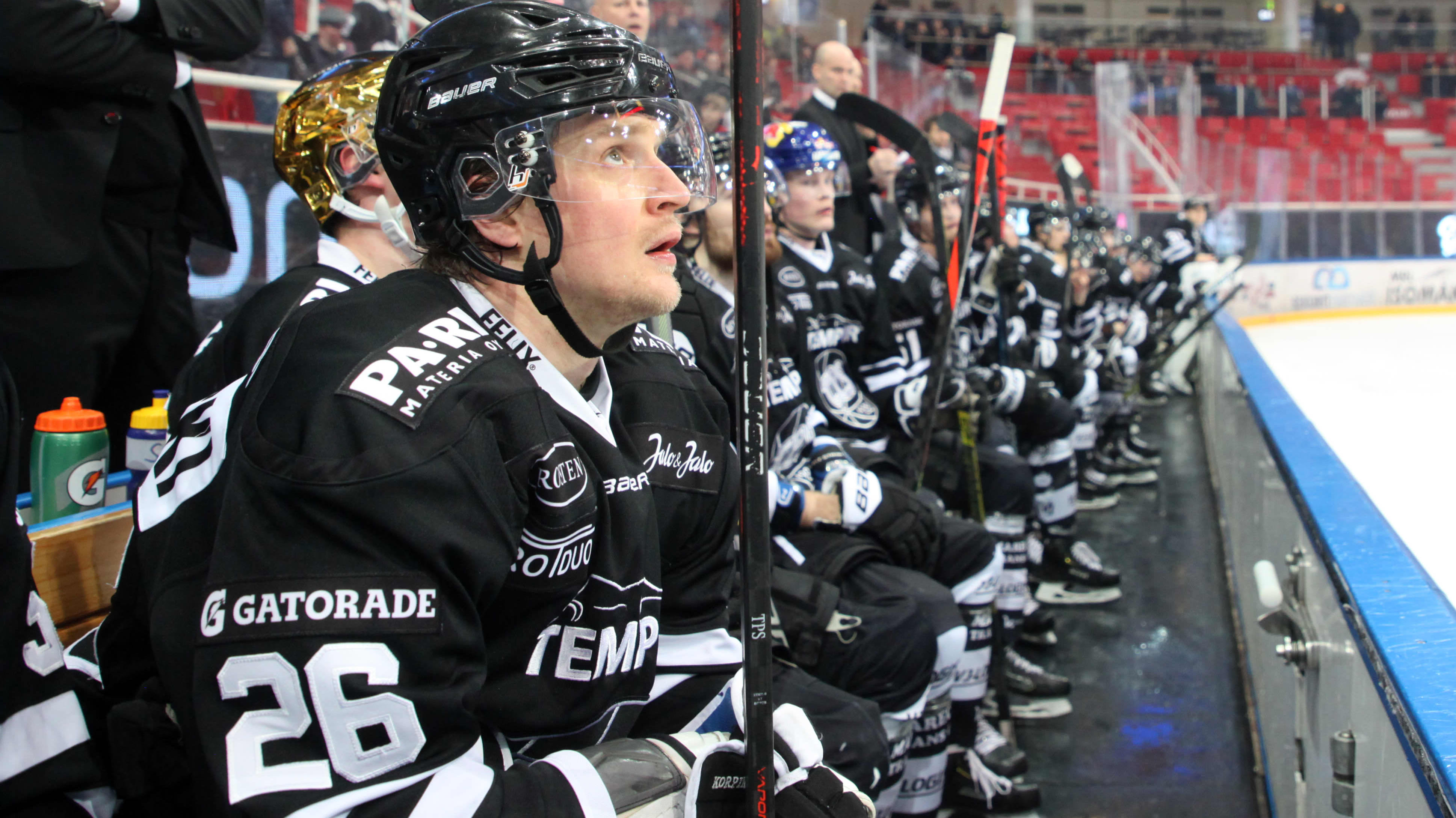 Lauri Korpikoski sitter på bytesbänken och tittar upp mot jumbotronen.