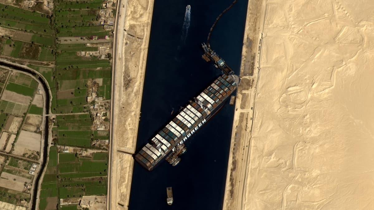 Poikittain kanavassa oleva laiva satelliitista kuvattuna.
