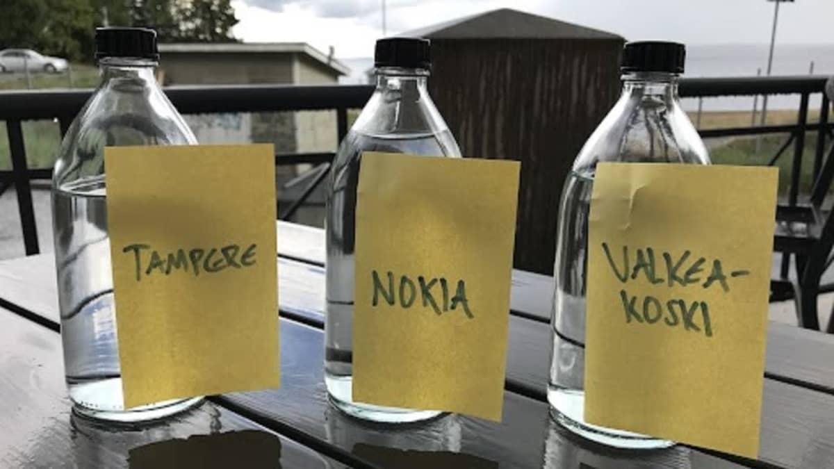 Kolme vesipulloa, joissa on vettä eri kunnista.