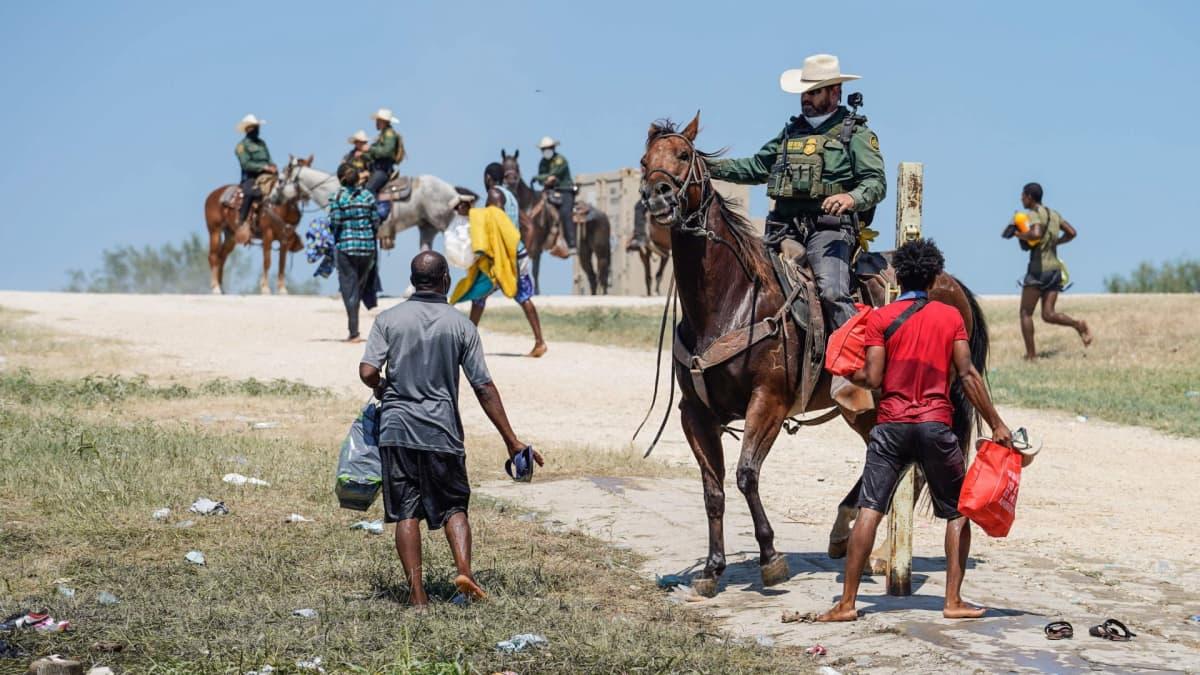 Yhdysvaltain rajavartija yrittää pysäyttää siirtolaisia Del Riossa.