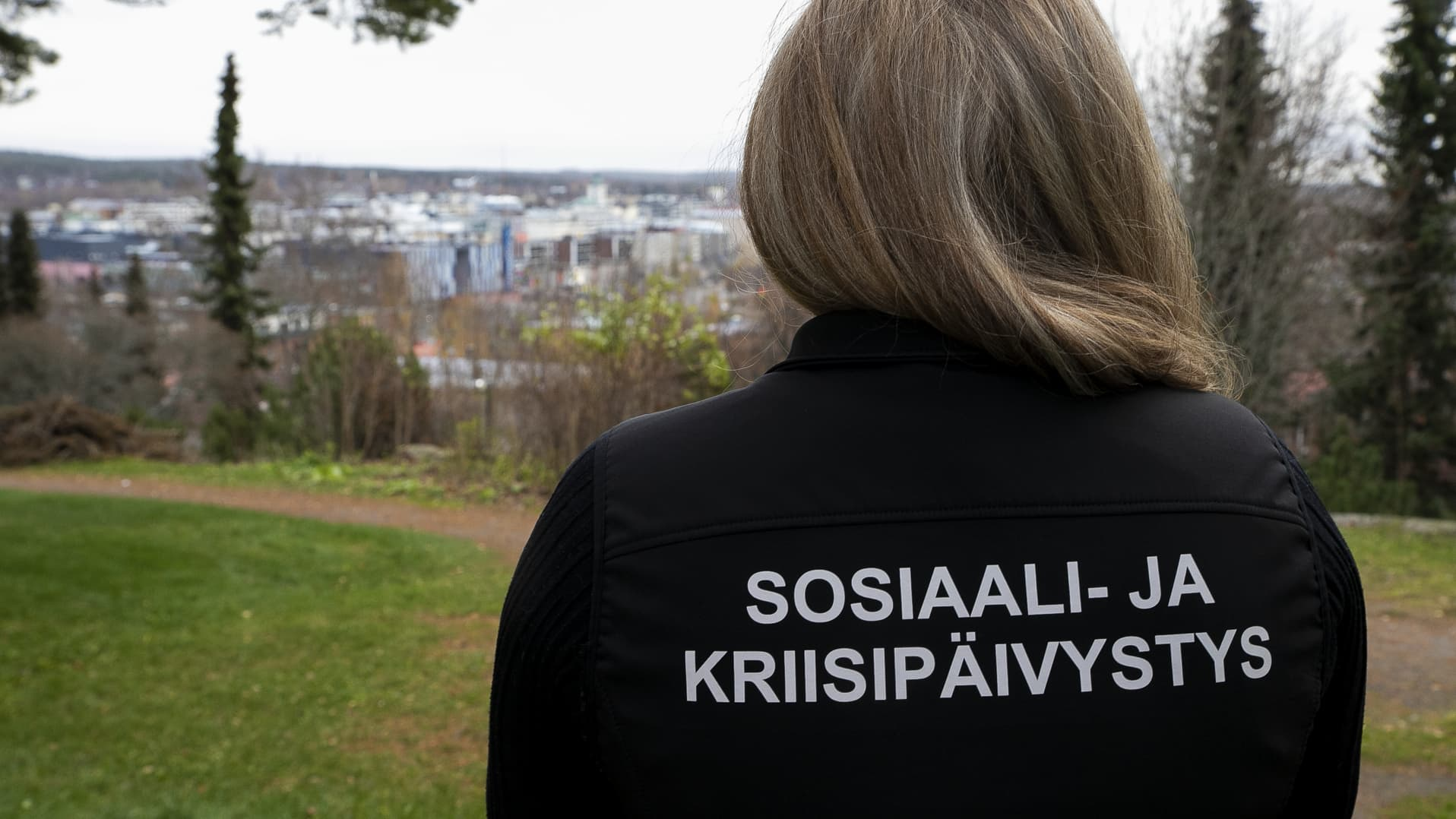 Nainen katselee syksyistä kaupunkia sosiaali- ja kriisipäivystys työntekjän takki yllään.