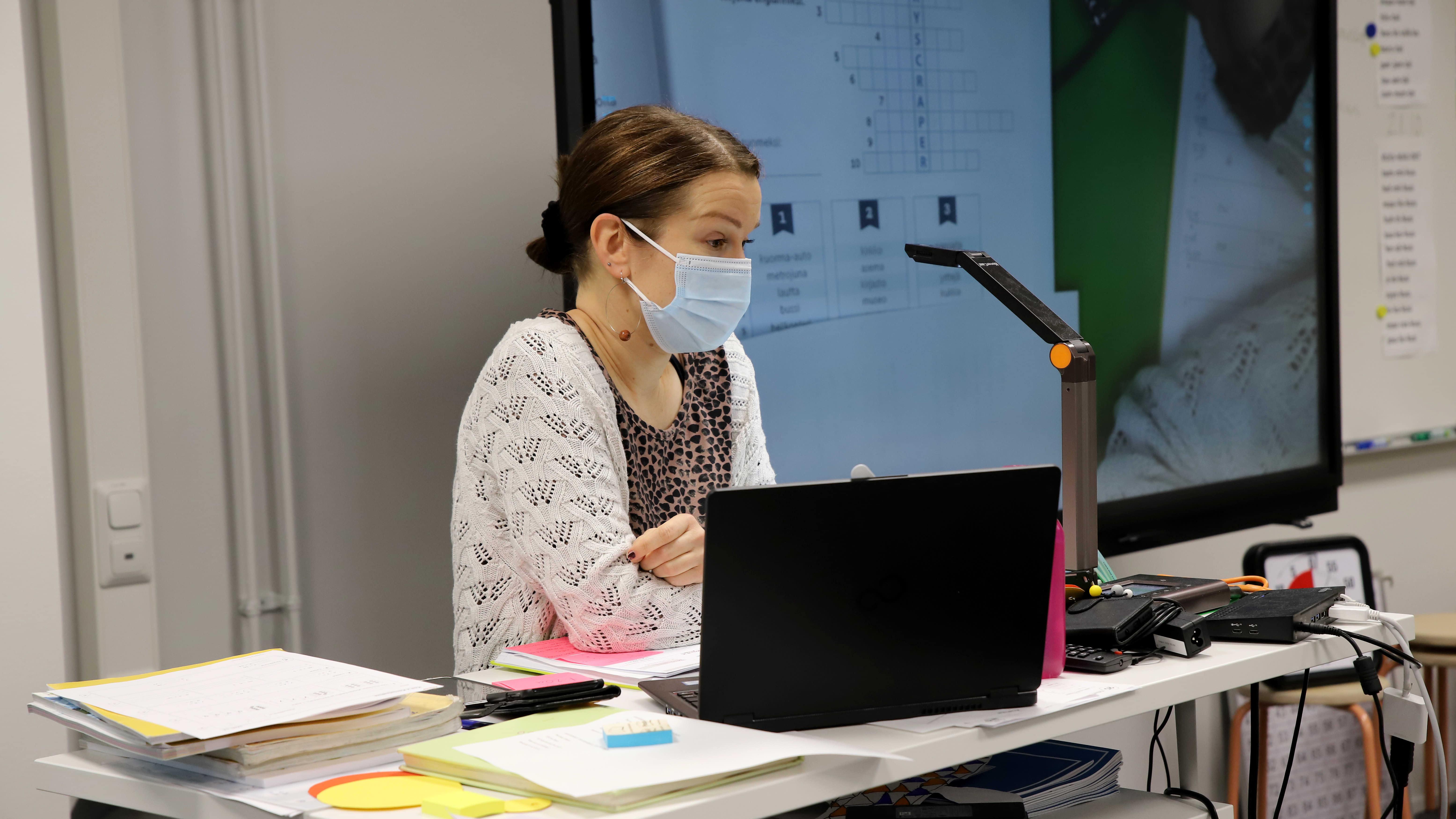 Erityisluokanopettaja Mari Puustinen opettaa oppilaita samanaikaisesti sekä etänä että luokassa. Kasvomaski kasvoilla, osa oppilaista on karanteenissa, oppilaita ei näy kuvassa.