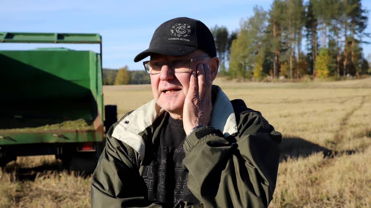 Maanviljelijä Ilpo Markkola lippahattu päässä, toinen käsi poskella seisoo pellolla, takana puimuri.