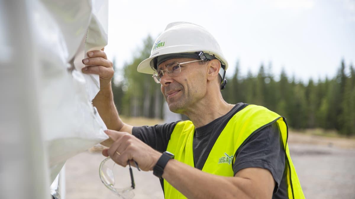 Markku Kortteisto tutkii tuulivoimalan osaa.