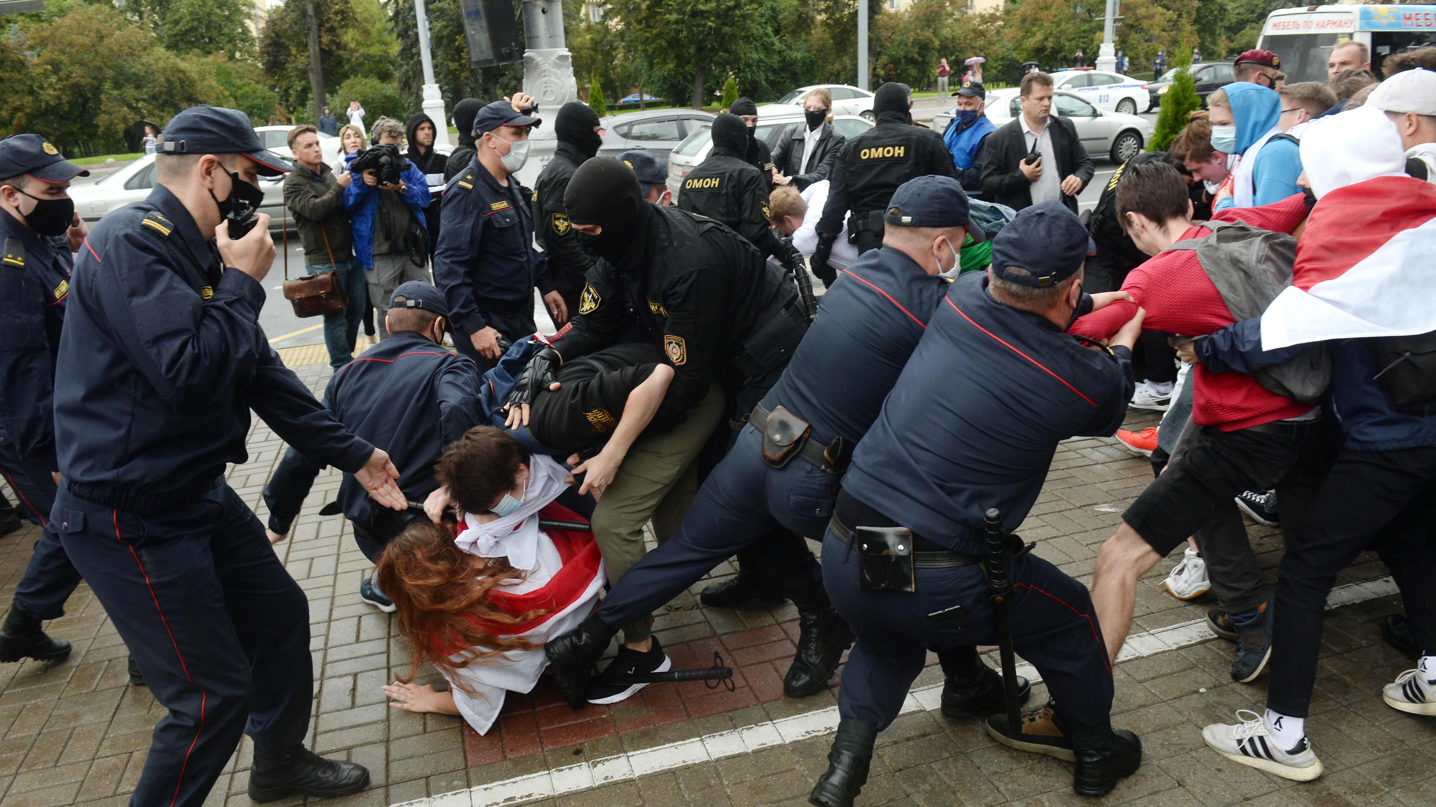 Valko-Venäjän poliisi ja OMON-erikoispoliisit taltuttavat opiskelijoita jotka osoittavat mieltä.