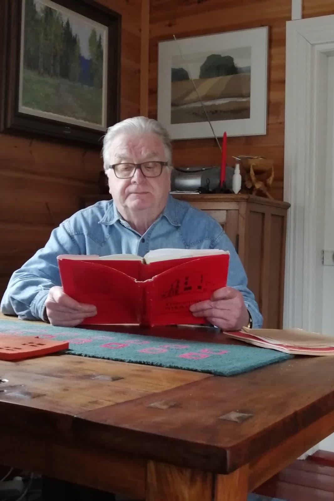 Mies lukee punaista kirjaa pöydän ääressä.