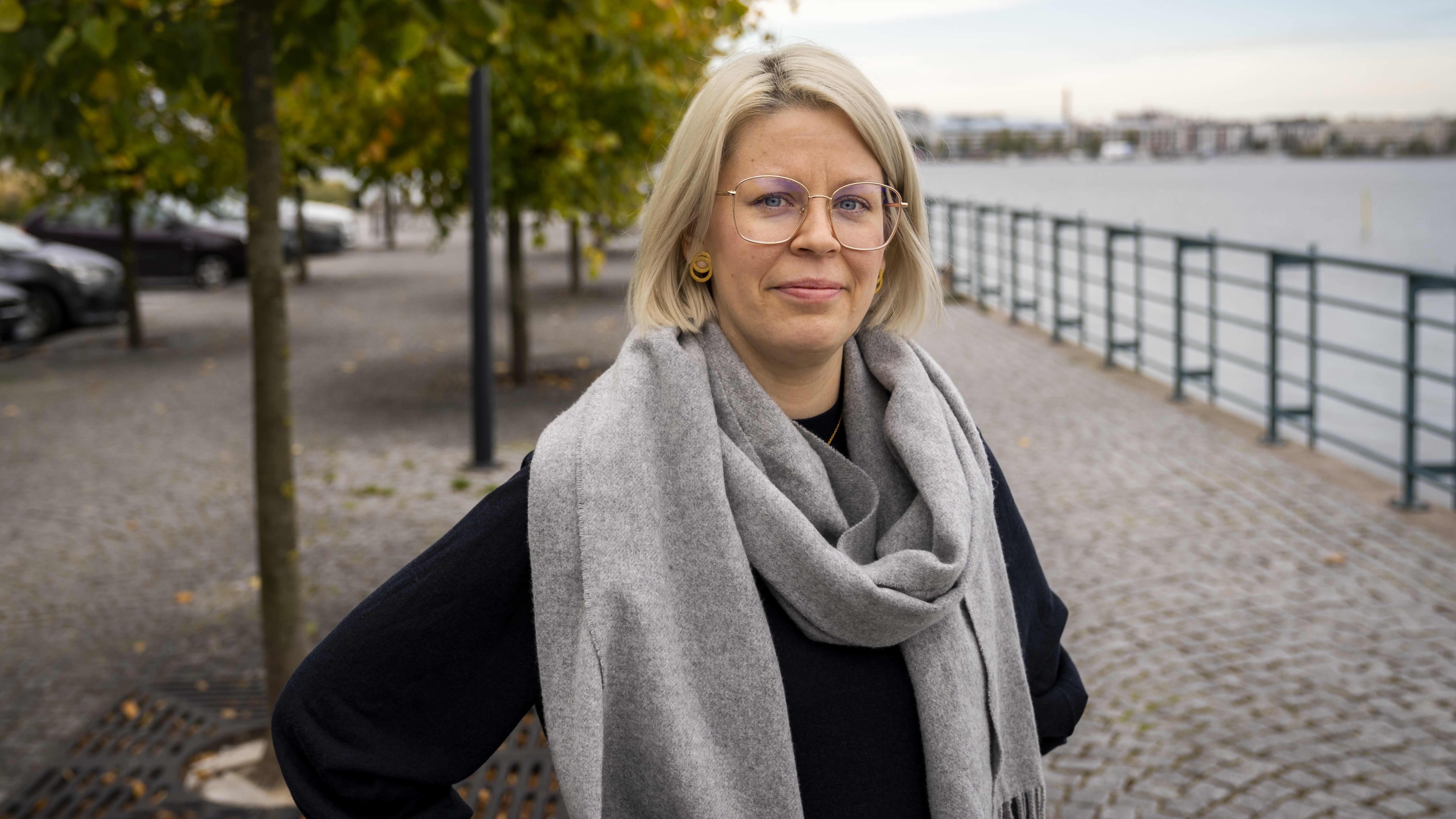 Psykologi Aino Juusola Jätkäsaaressa, taustalla ruskaisia puita ja merta.