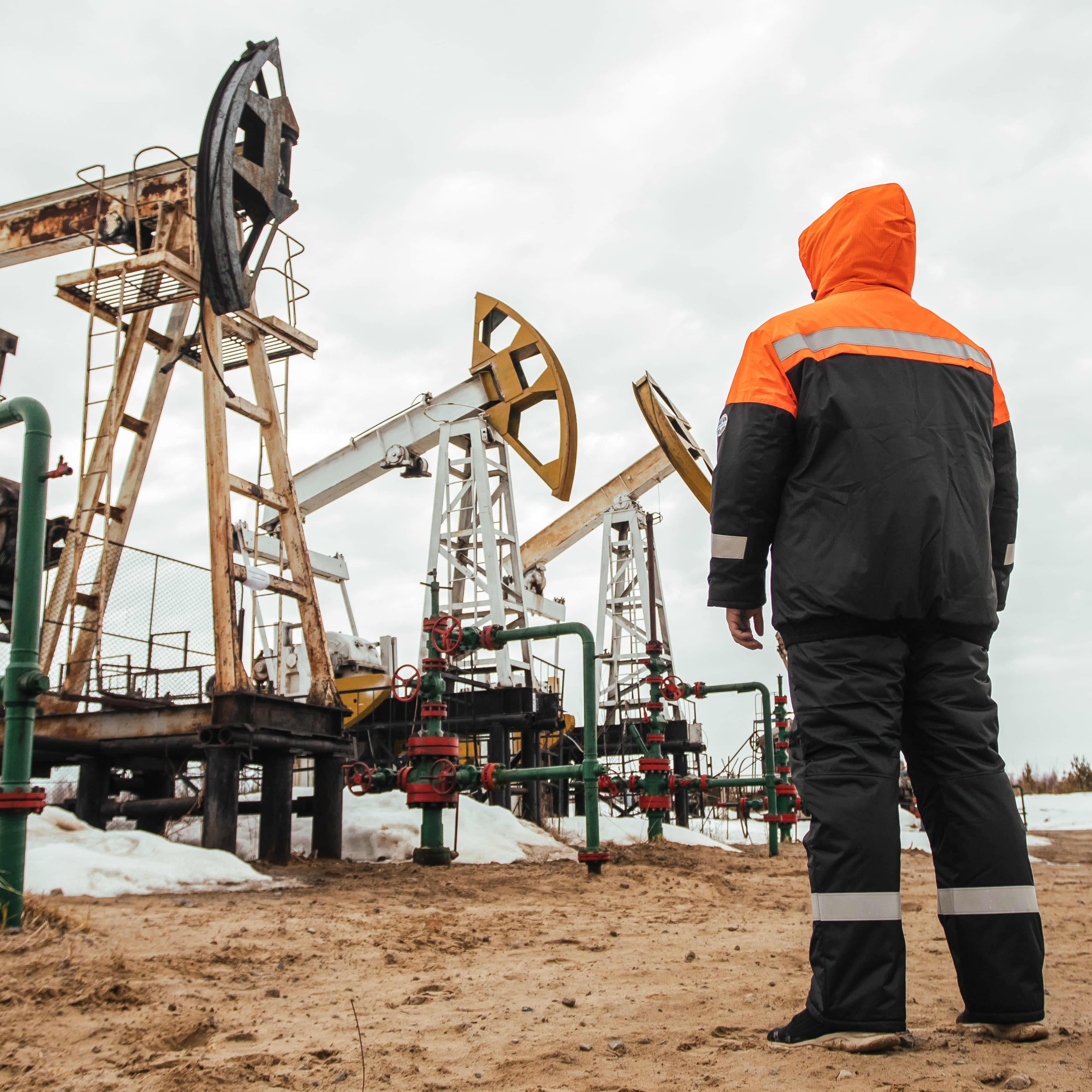 Henkilö katselee öljypumppuja Venäjän Surgutissa.