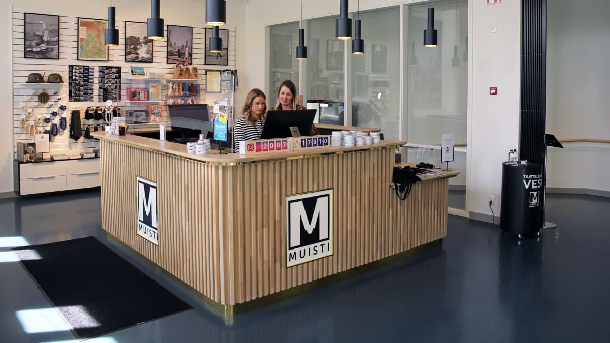 Mikkelissä sijaitsevan tiedekeskus Muistin aula. Kaksi työntekijää tiskin takana.