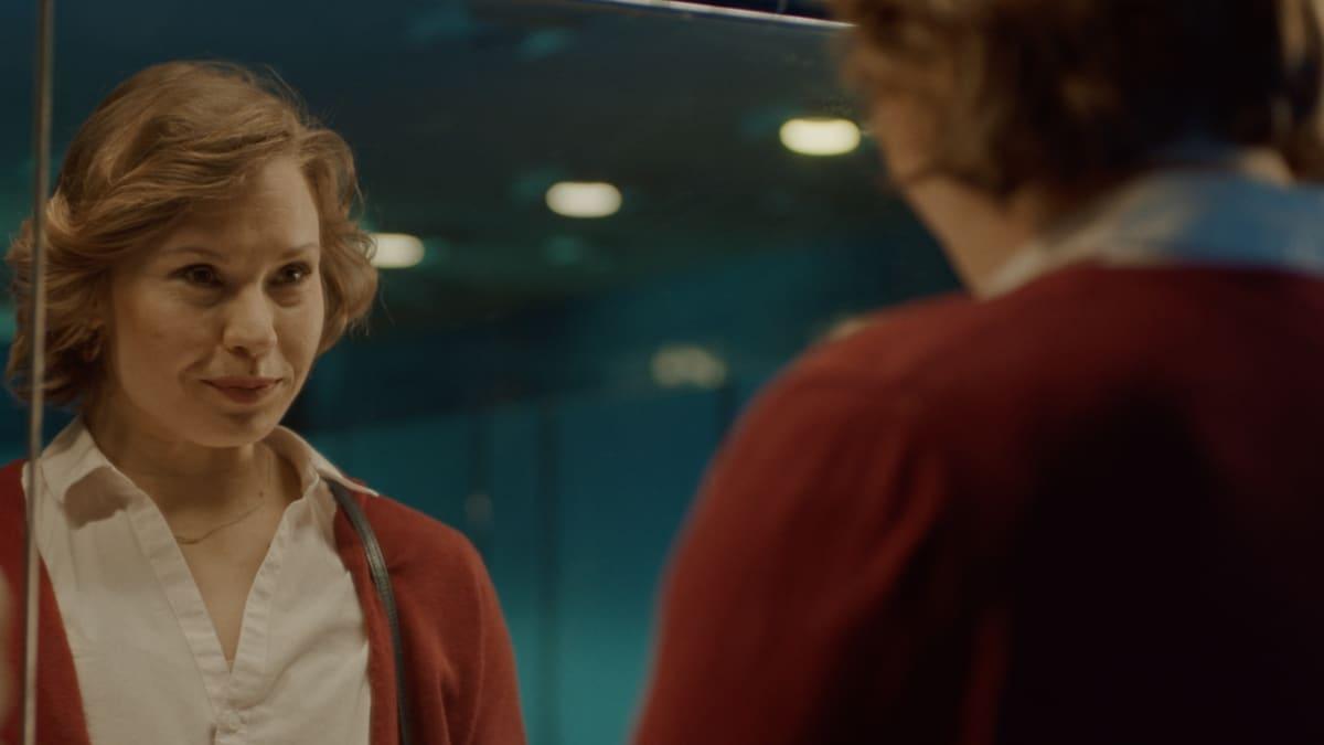 Katja ser sig själv i spegeln på firmafesten.