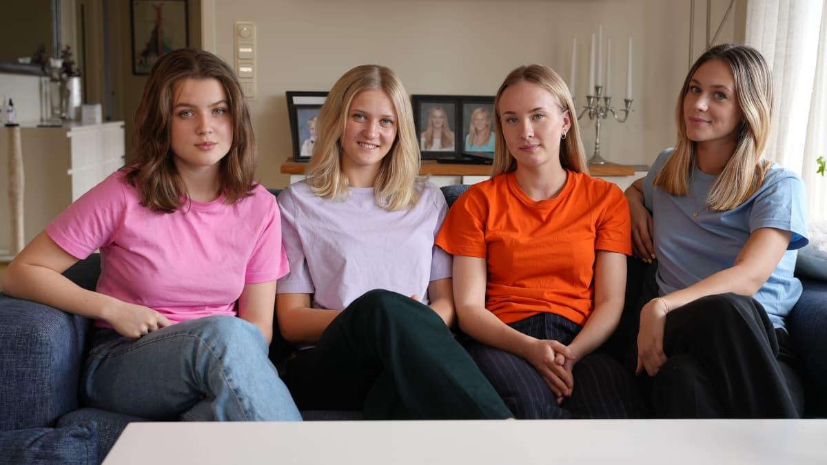 neljä tyttöä istuu sohvalla ja katsoo kameraan
