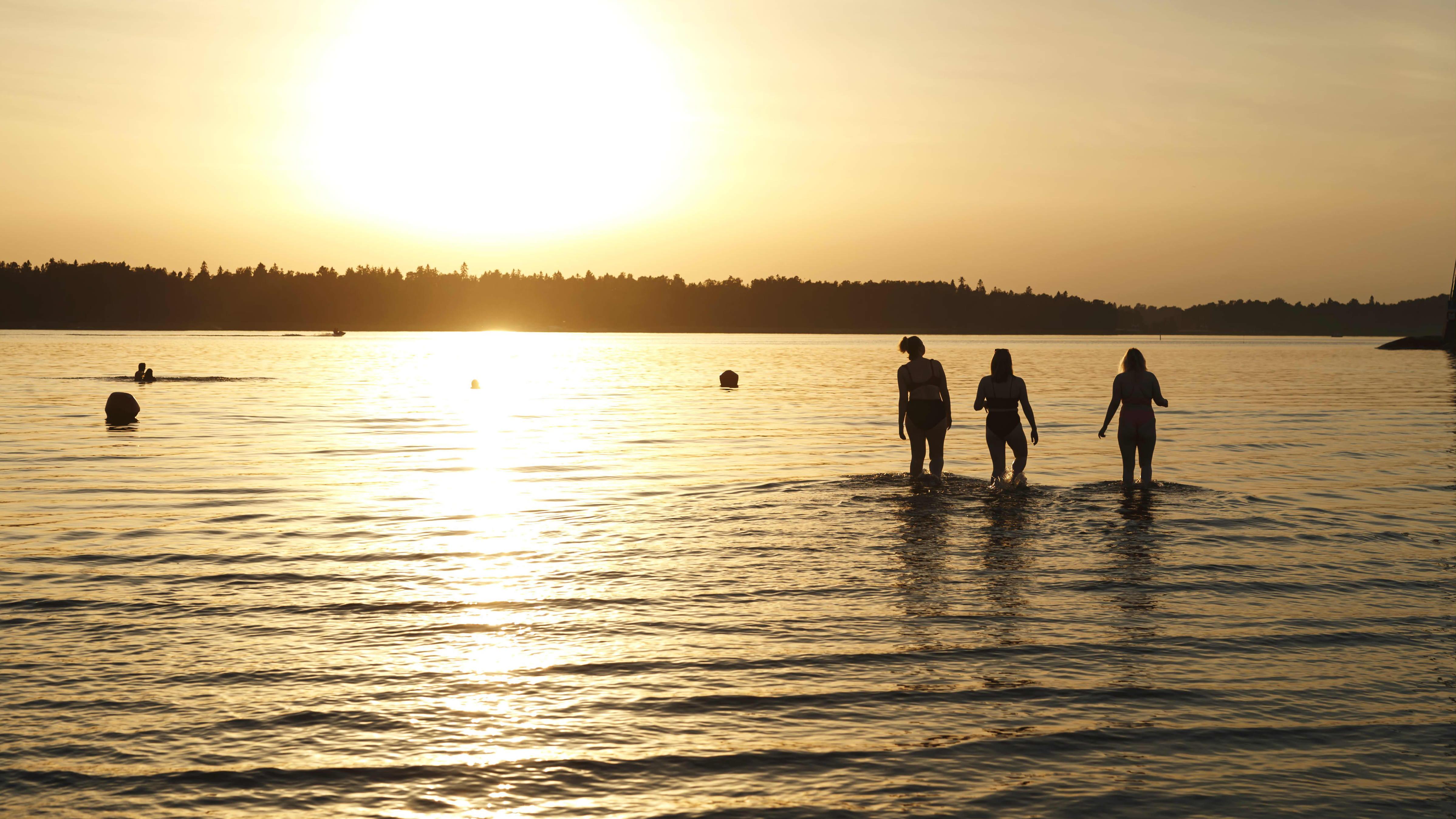 Ilta-aurinko paistaa Hietaniemen uimarannalla Helsingissä.