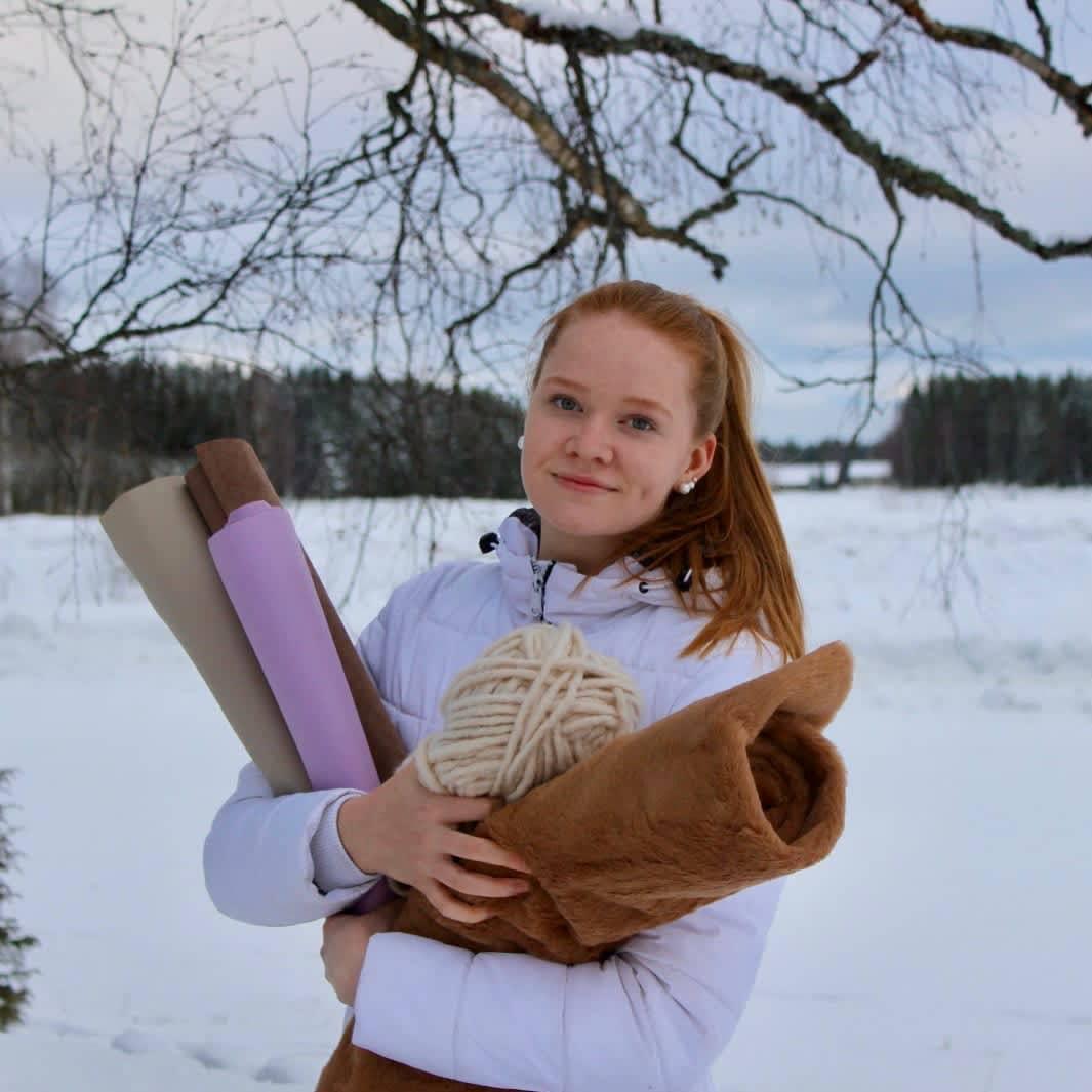 Tyttö pitää sylissään keppihevosen tekoon tarvittavia välineitä.