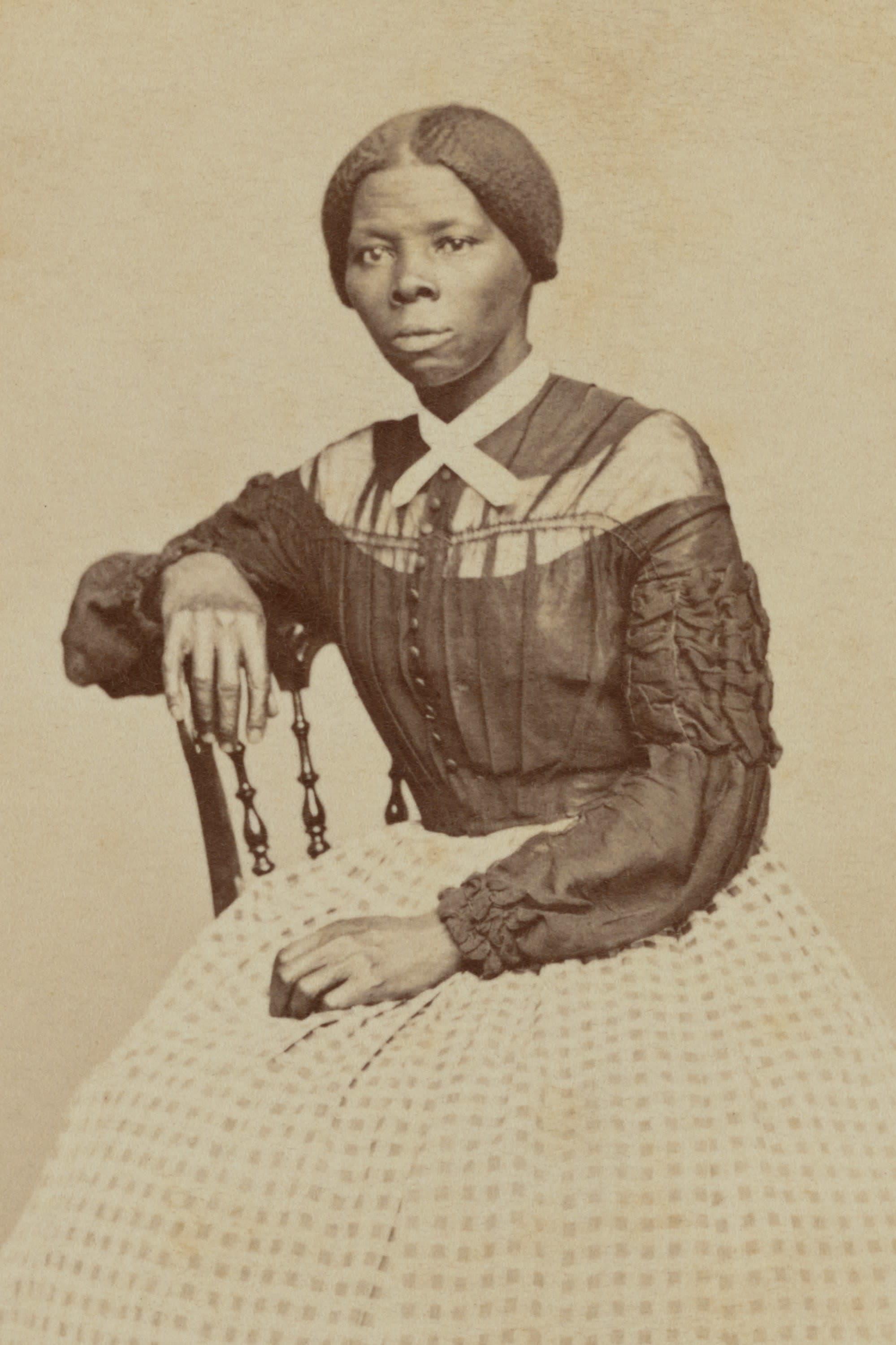 Mustavalkoisessa valokuvassa Harriet Tubman istuu tuolilla oikea käsi tuolin selkänojalla, vasen käsi sylissään. Hänellä on suuri ruutukuvioinen hame.