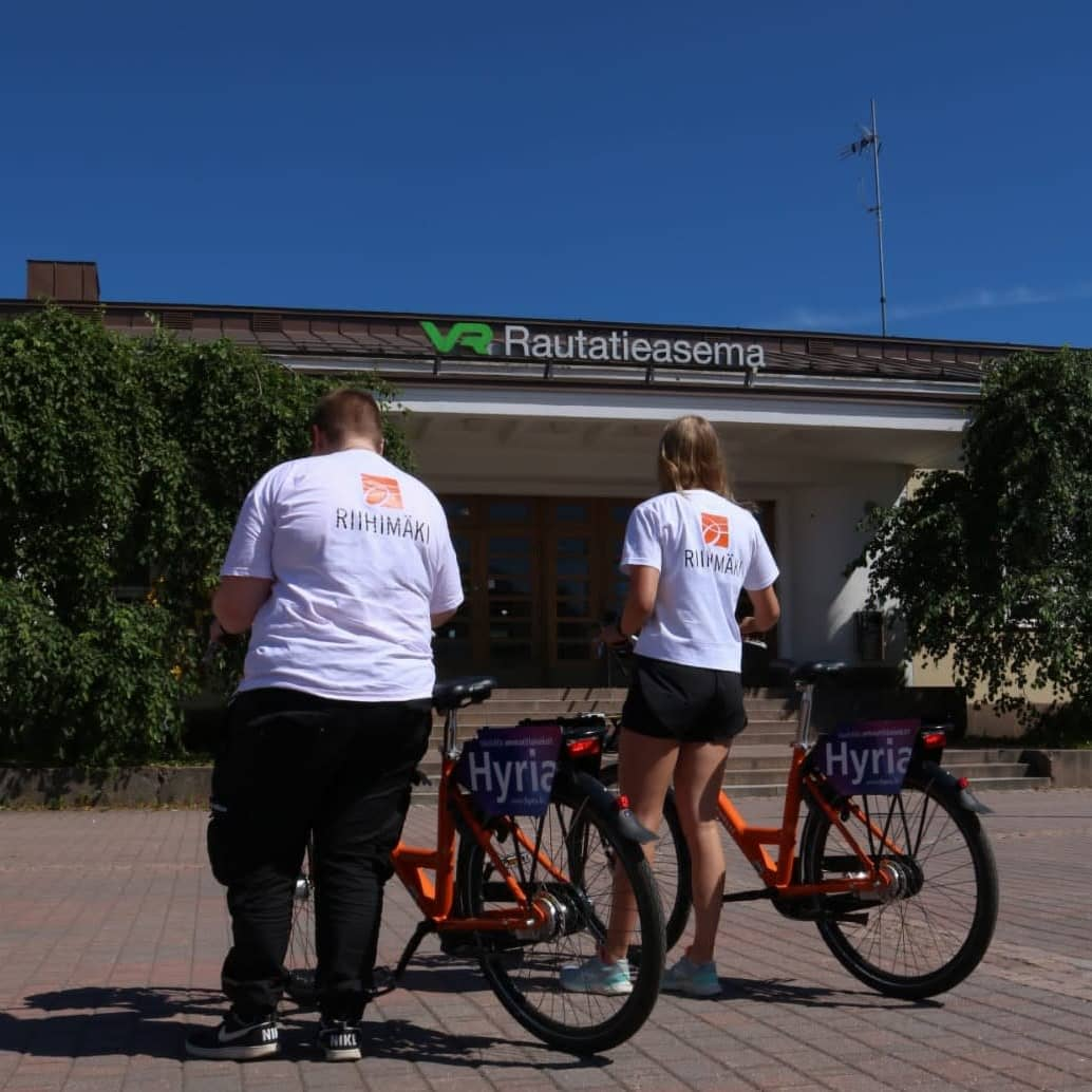Kaksi nuorta valkoisissa t-paidoissa polkupyörien vieressä.
