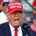 Trump punaisessa lippalakissa puhuu kannattajilleen.